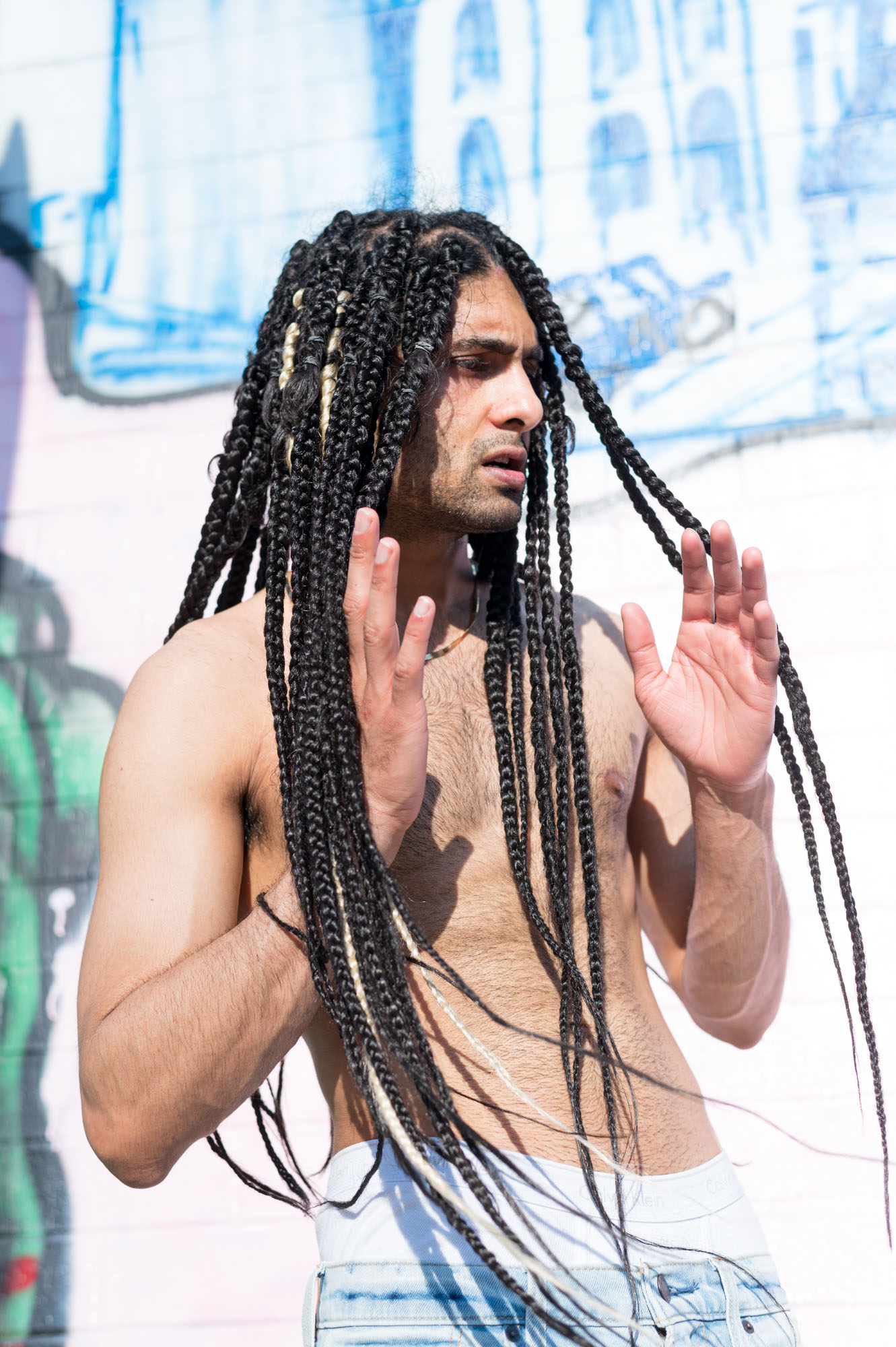 a model parts his braids on a sunny day in Portland, Oregon