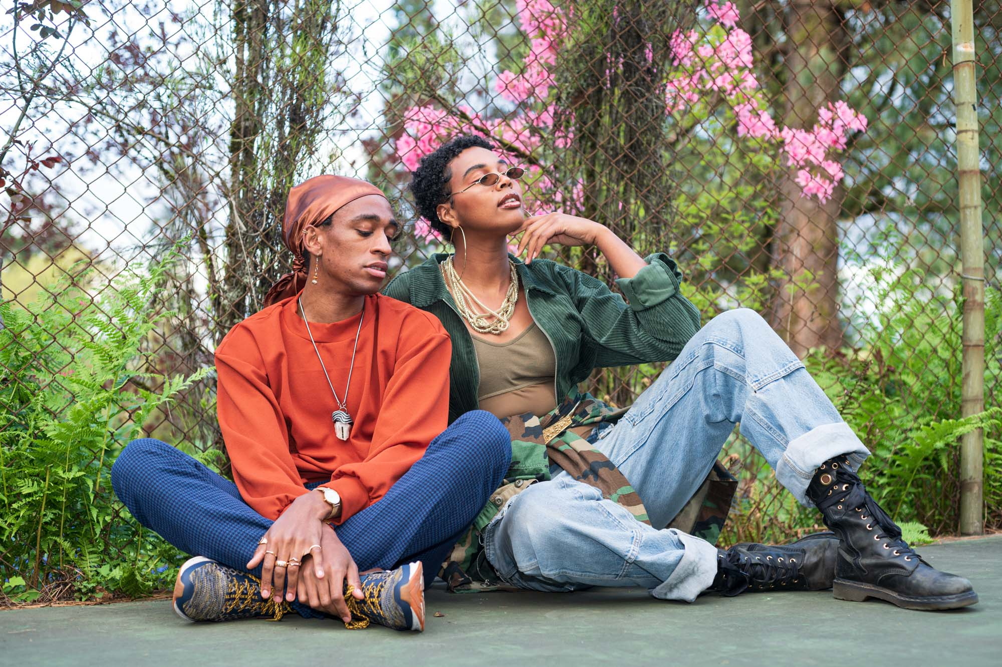 two models sit against a chain link fence, surrounded by plant life