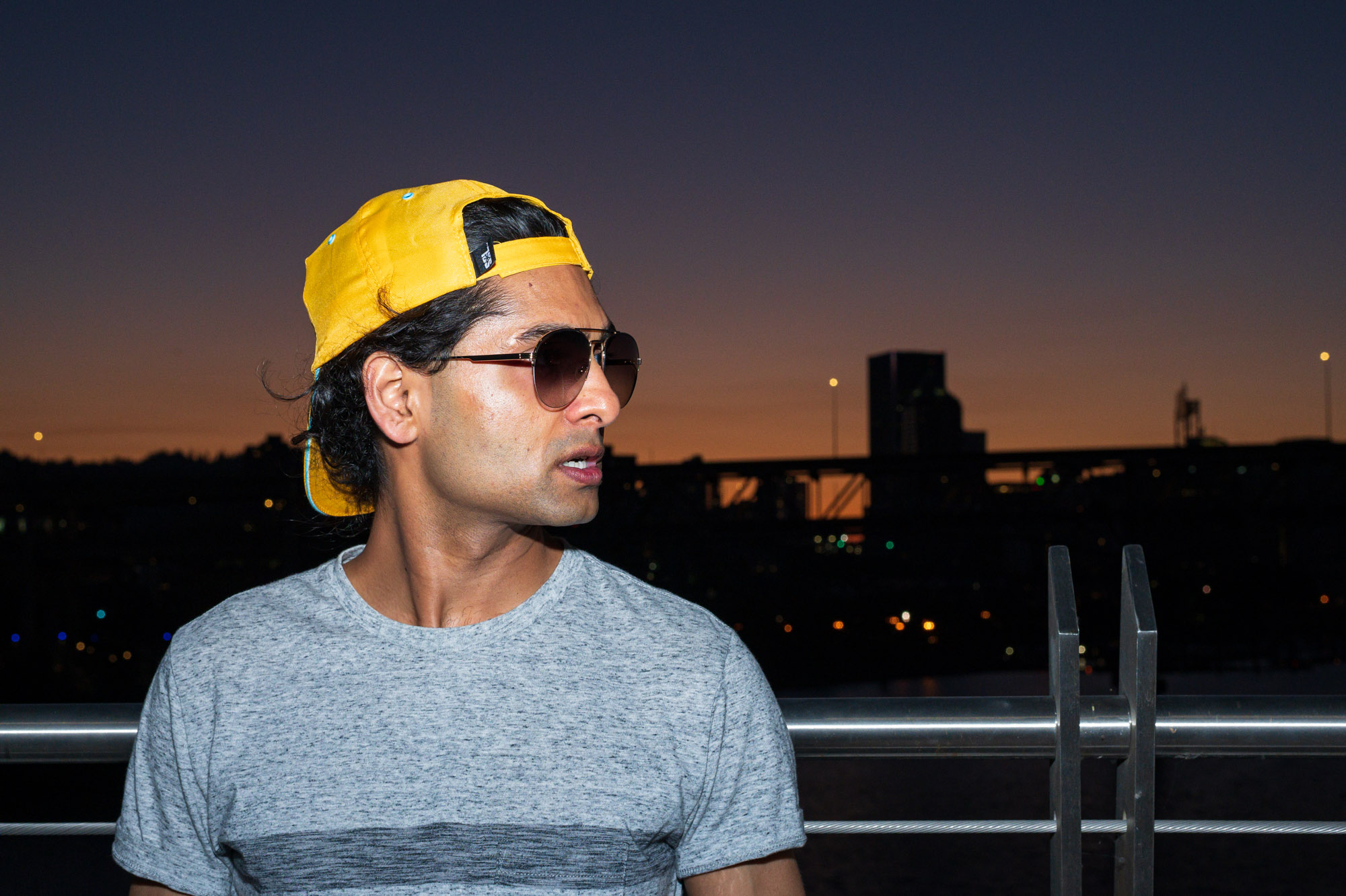 a man in a yellow ballcap stands on a bridge as the sun goes down