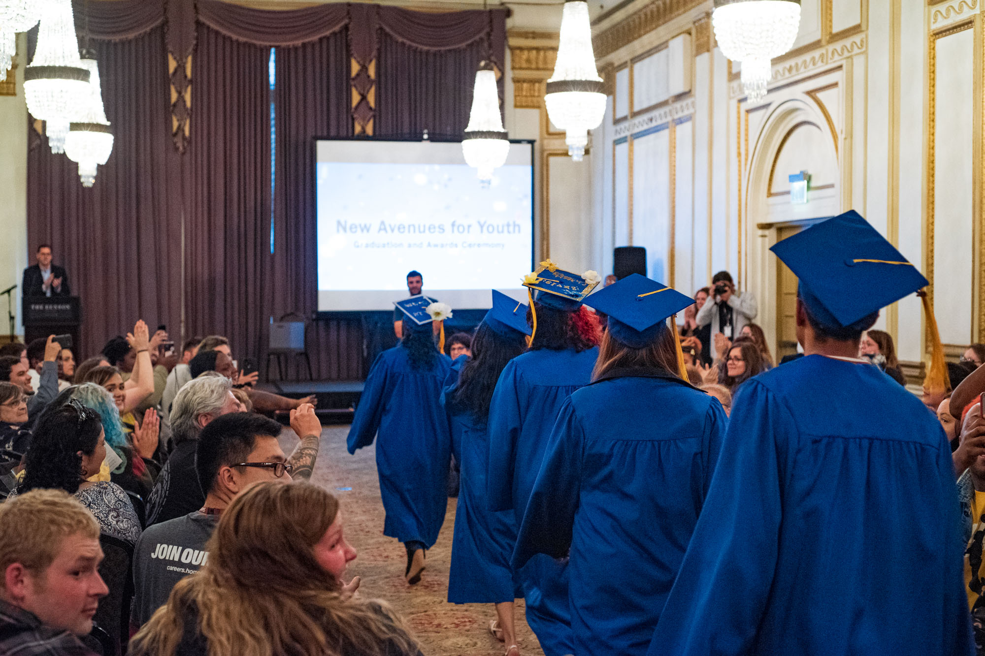 graduates walk down the aisle in their caps and gowns