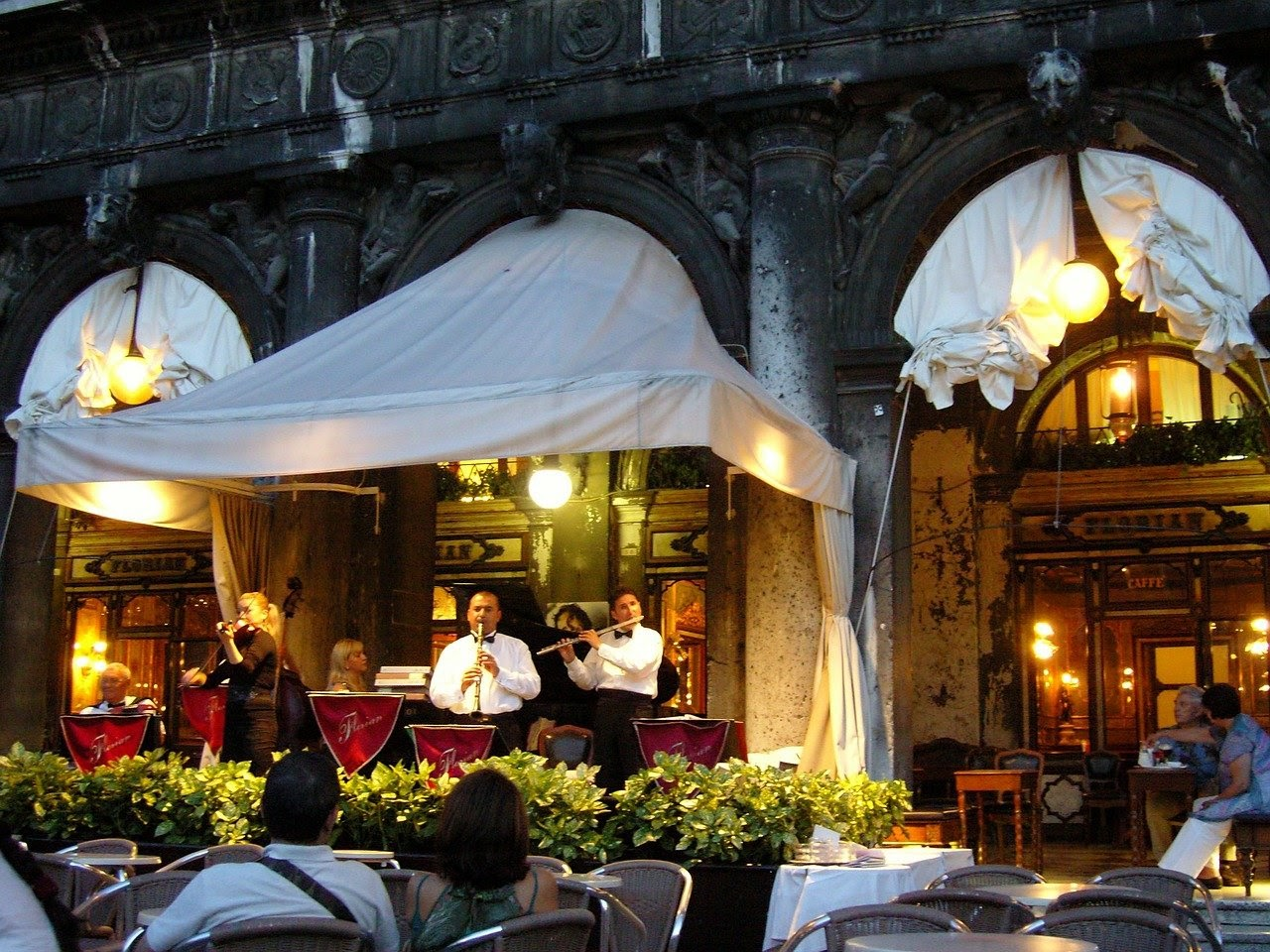 A group of classical musicians markets their group by performing live at a nice restaurant.