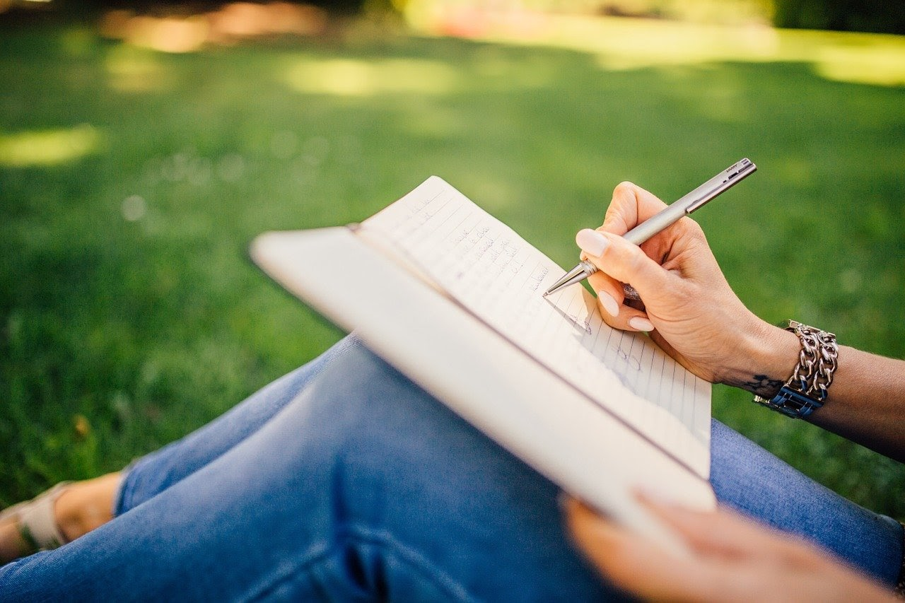 A content creator sits in the grass and journals after gaining new content inspiration