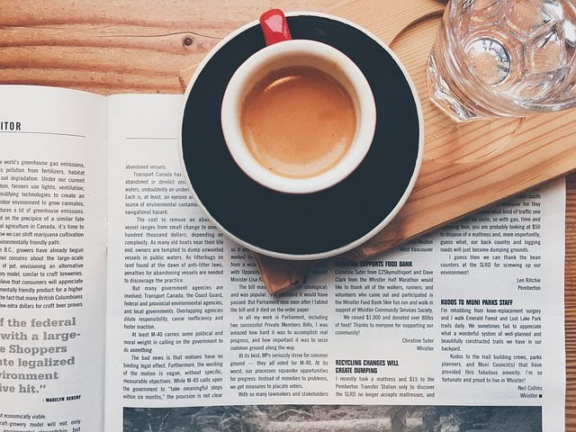 a newspaper and a hot coffee
