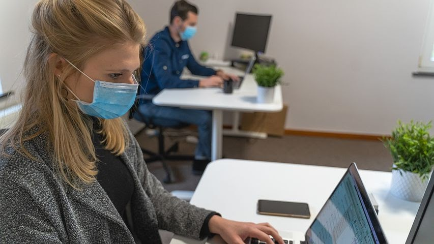 two coworkers work socially distanced wearing masks