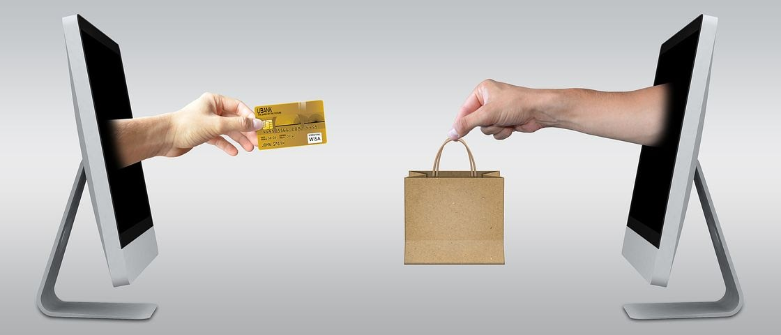 two screens represent an ecommerce transaction, exchanging a credit card (money) for goods