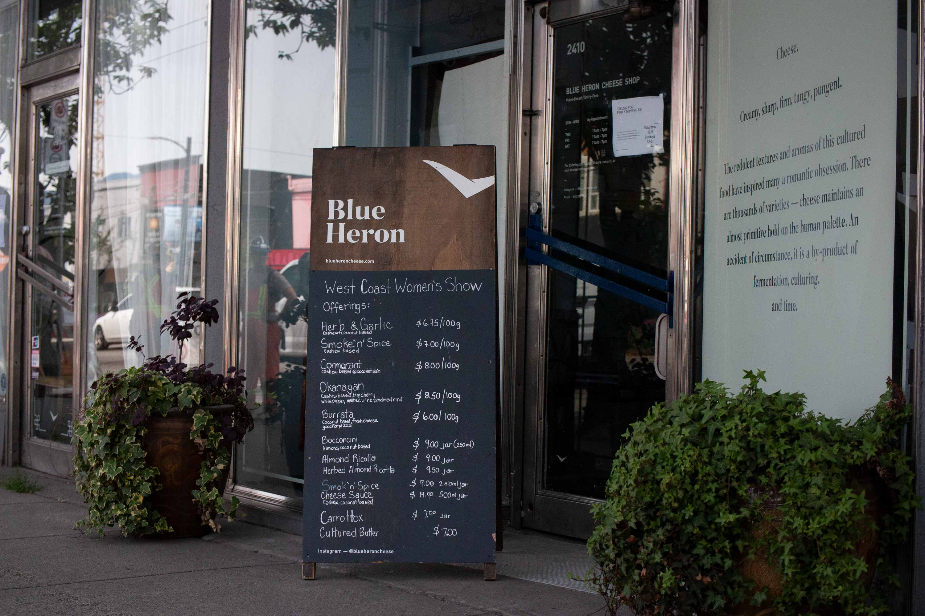 Blue Heron storefront with plants, hand painted sandwich board and windows — by Dima Yagnyuk.