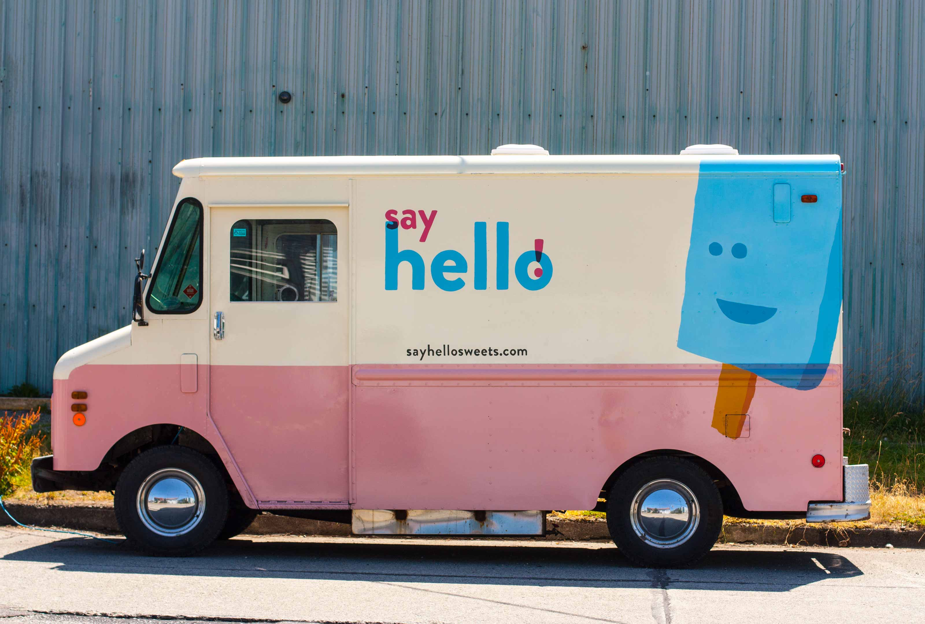 Say Hello pink and white ice cream truck with a vibrant blue logo and ice cream bar wrapping around the corner of the vehicle — by Dima.