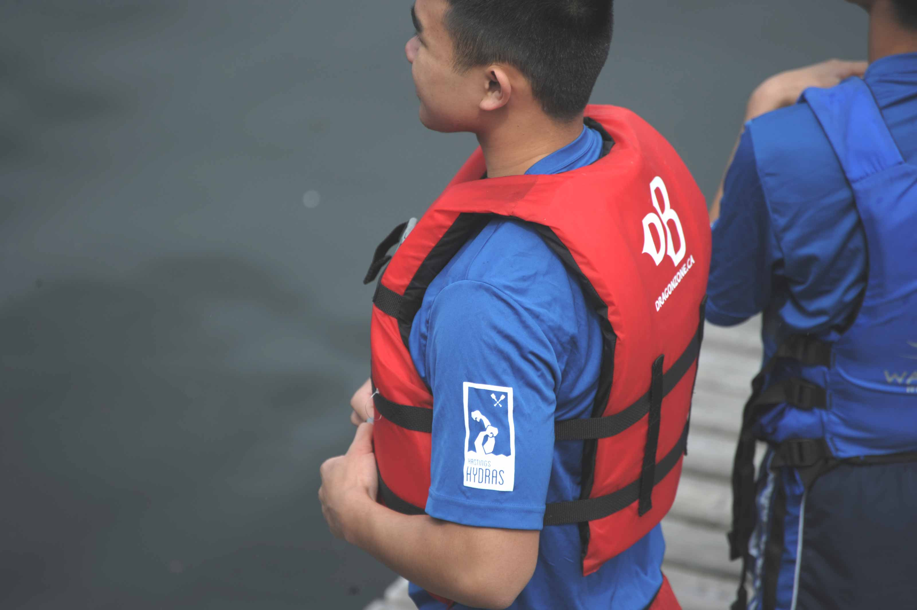 Dragon Boat team member wearing a blue shirt with Hasting Hydras logo on the sleeve — by Yagnyuk.