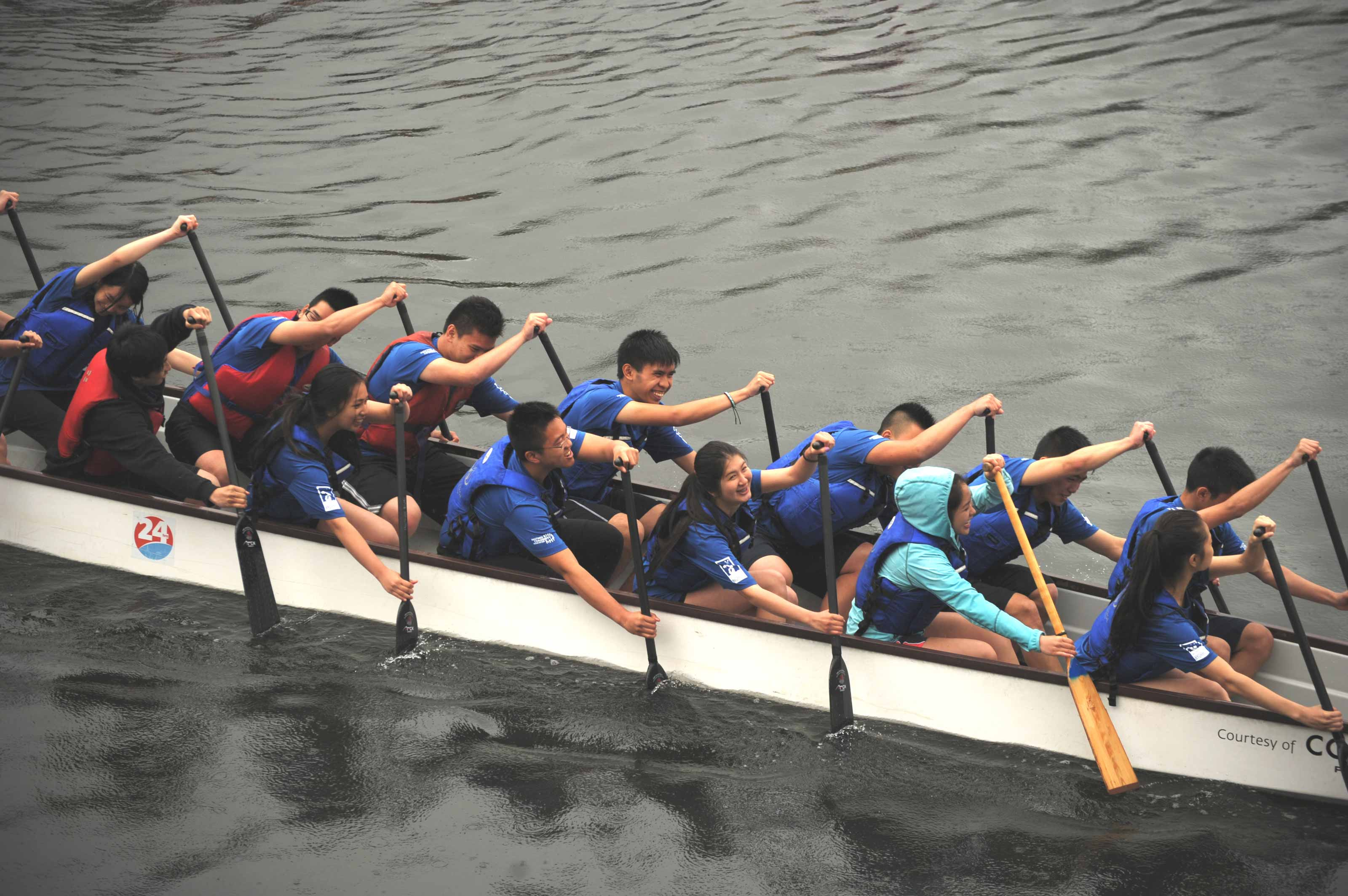 Hastings Hydras dragon boat team racing on the water in the False Creek, Vancouver BC, while wearing the blue branding Hasting Hydras jerseys — by Yagnyuk.
