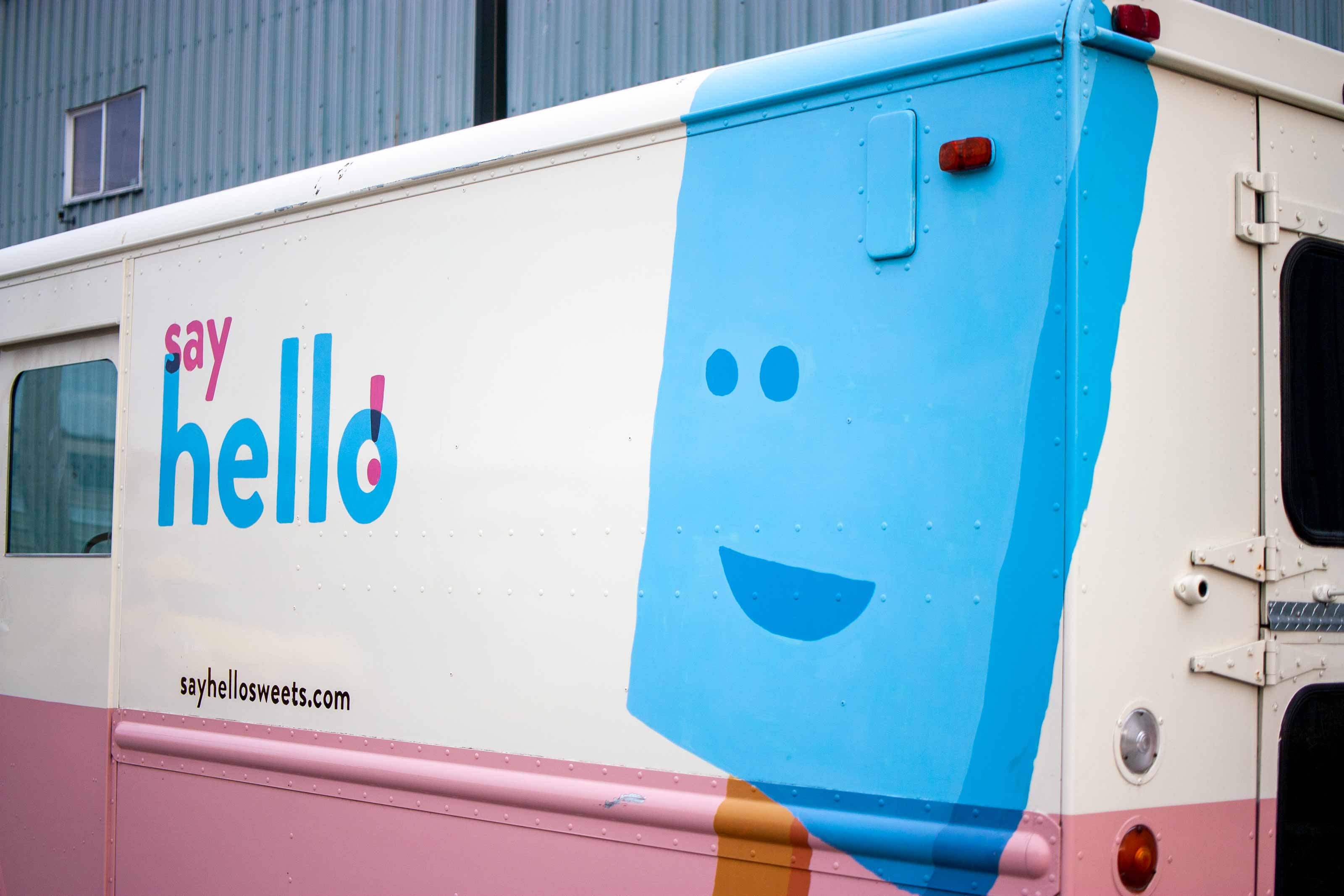 Say Hello Truck with a large blue popsicle wrapped around the corner of a cream and pink truck — by Yagnyuk.