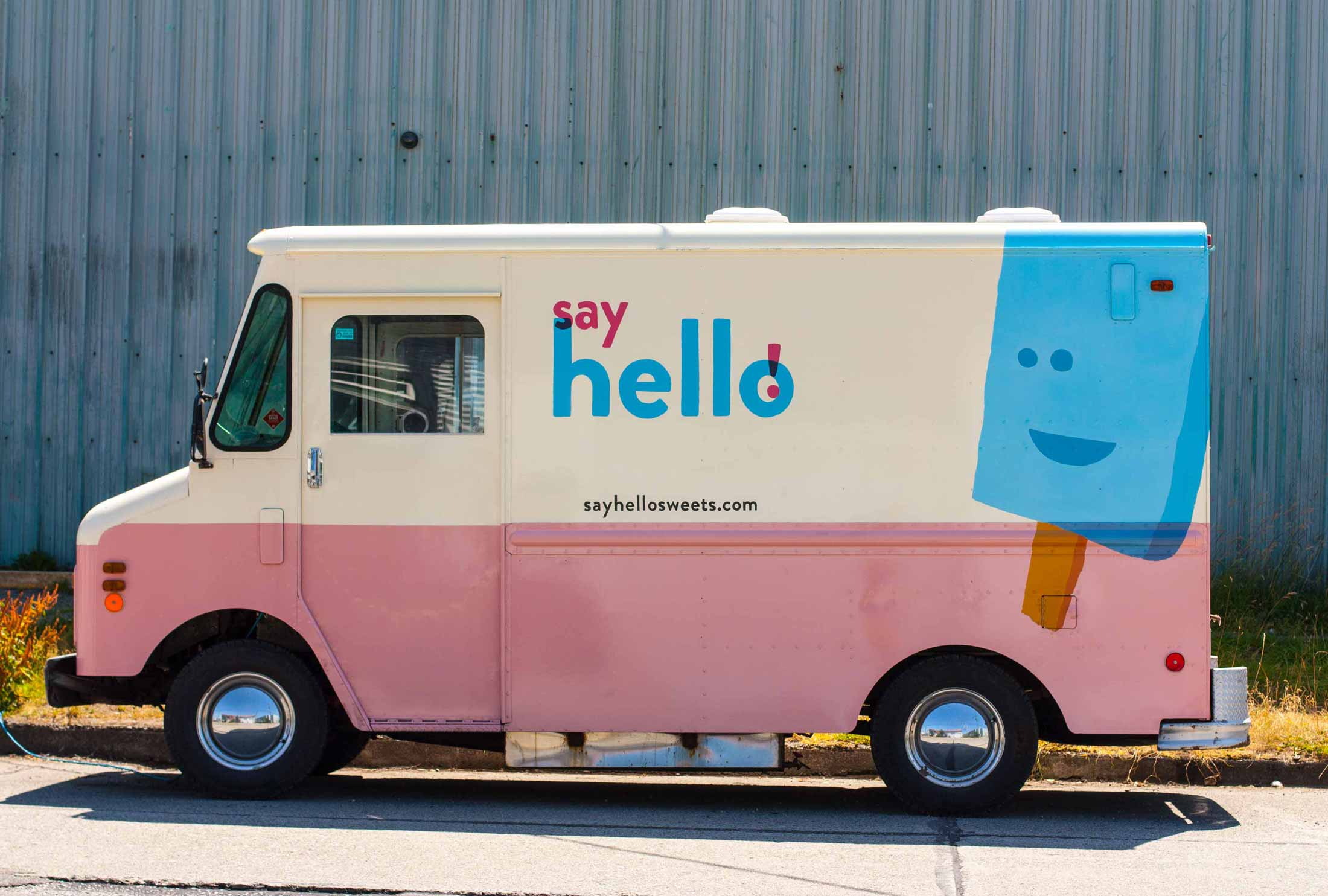 Pink bottom and cream top truck with Say Hello Logo and blue popsicle against a pink and cream background — by Yagnyuk.