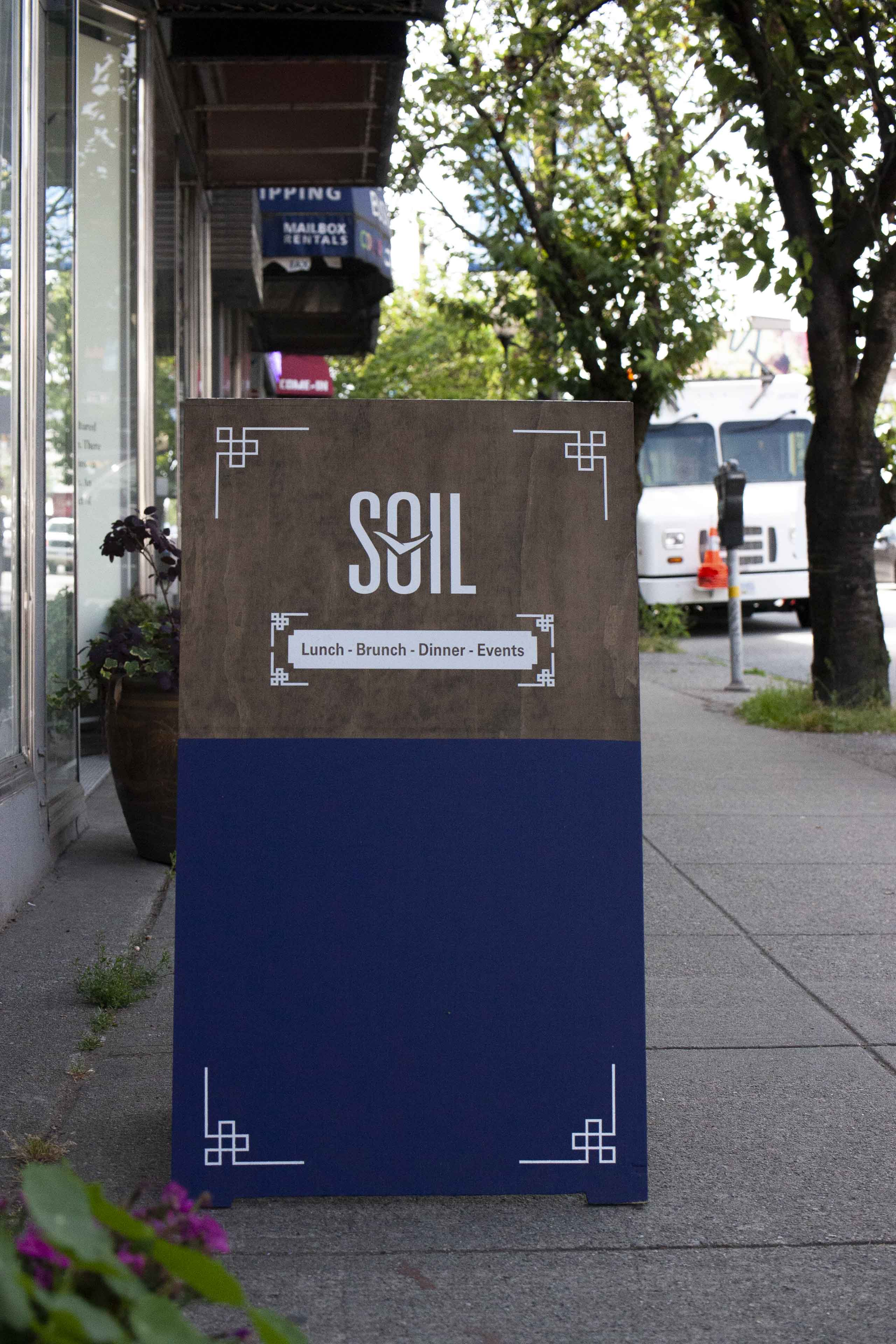 SOIL Sandwich board with the Main street alleyway in the background — by Yagnyuk.