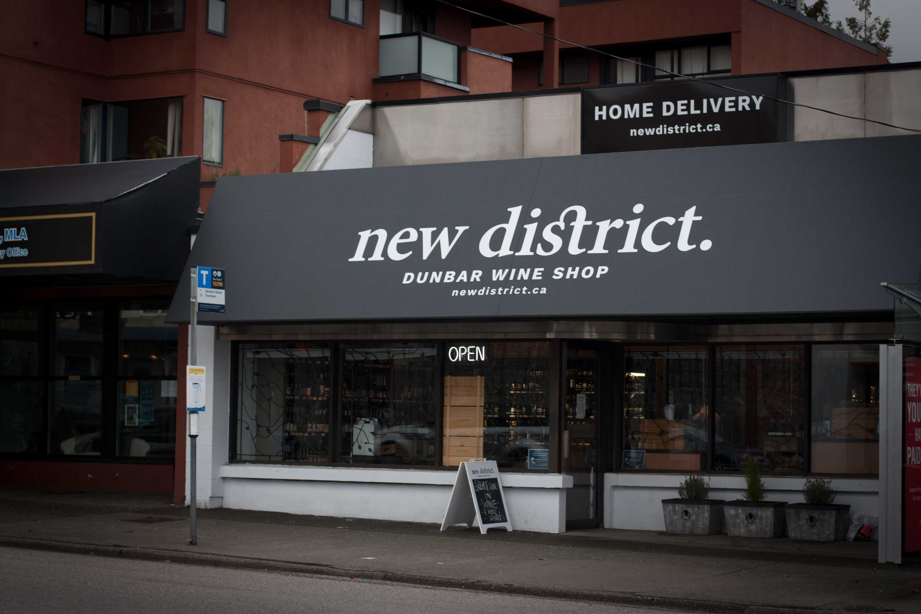 New District Wine Shop exterior with black awning featuring a white logo, and white exterior with packaging and wines showing through — by Dima Yagnyuk.