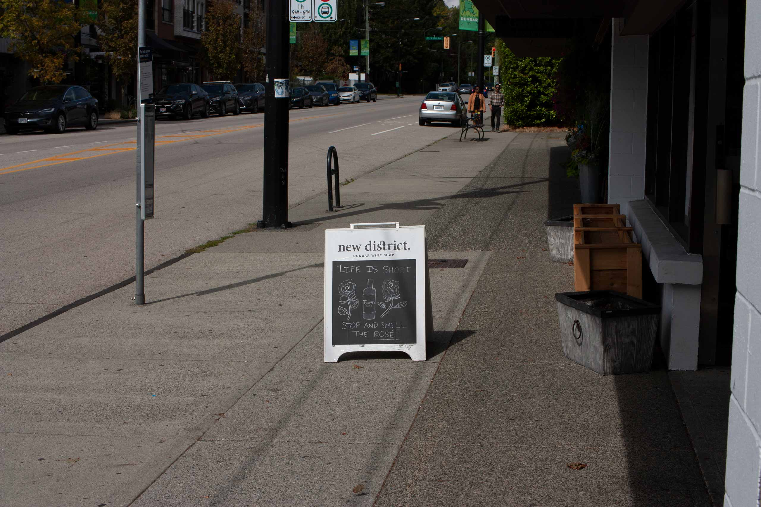 New District sandwich board in front of a sunlit store — by Yagnyuk.