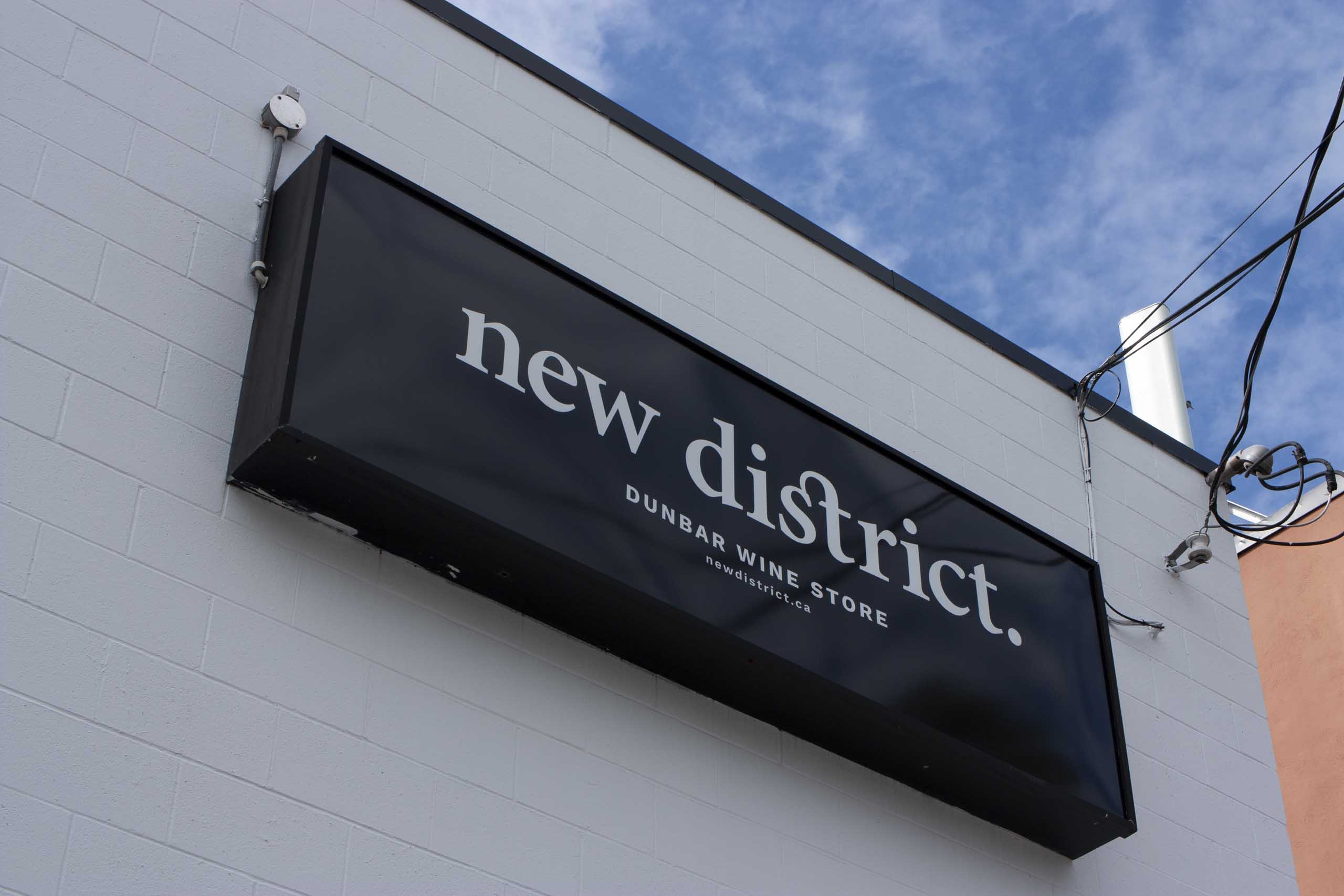 New District lighbox sign in white on black near the top of the building — by Yagnyuk.