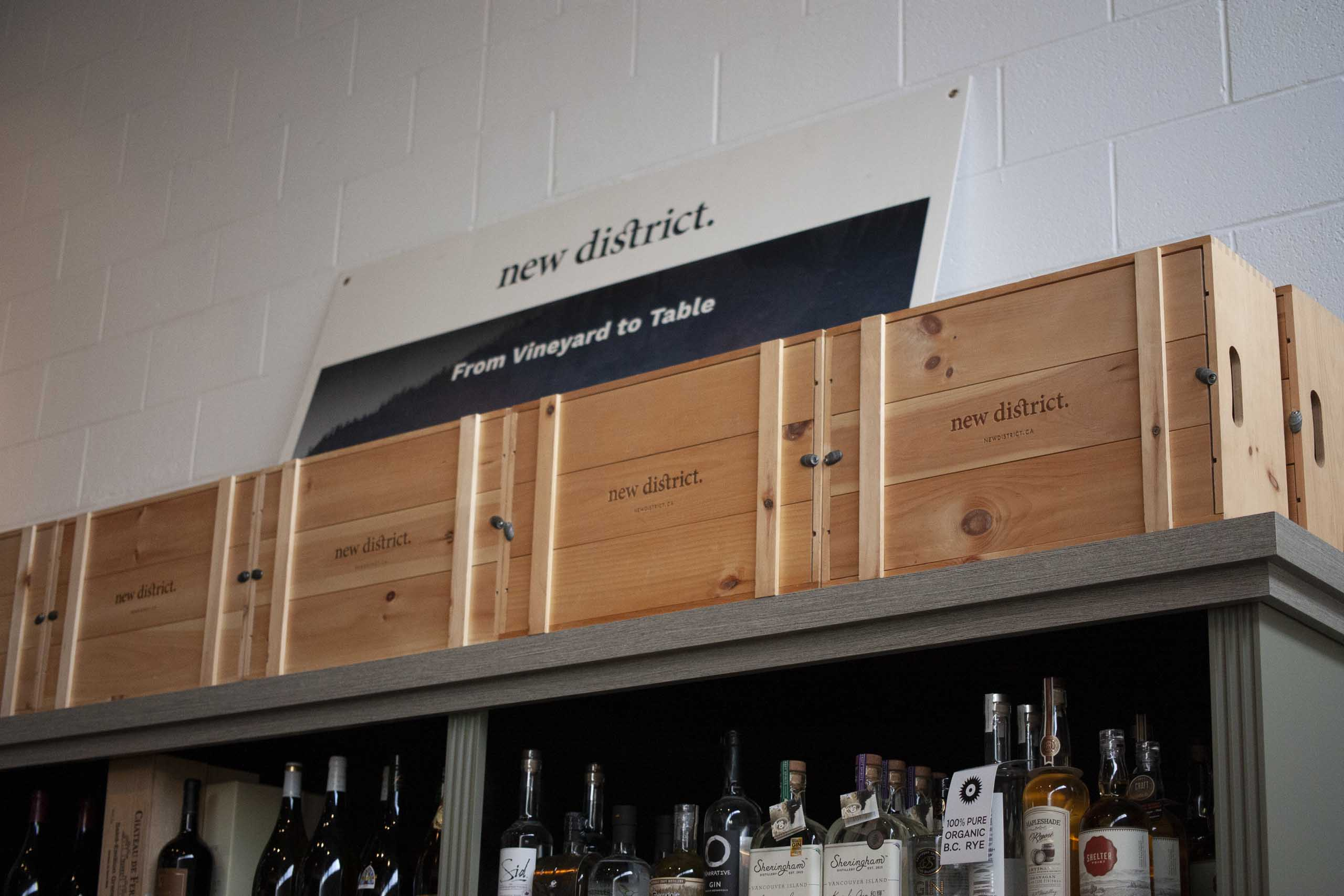New District Packaging crates on top of stained wood shelving against a a white cinderblock wall — by Yagnyuk.