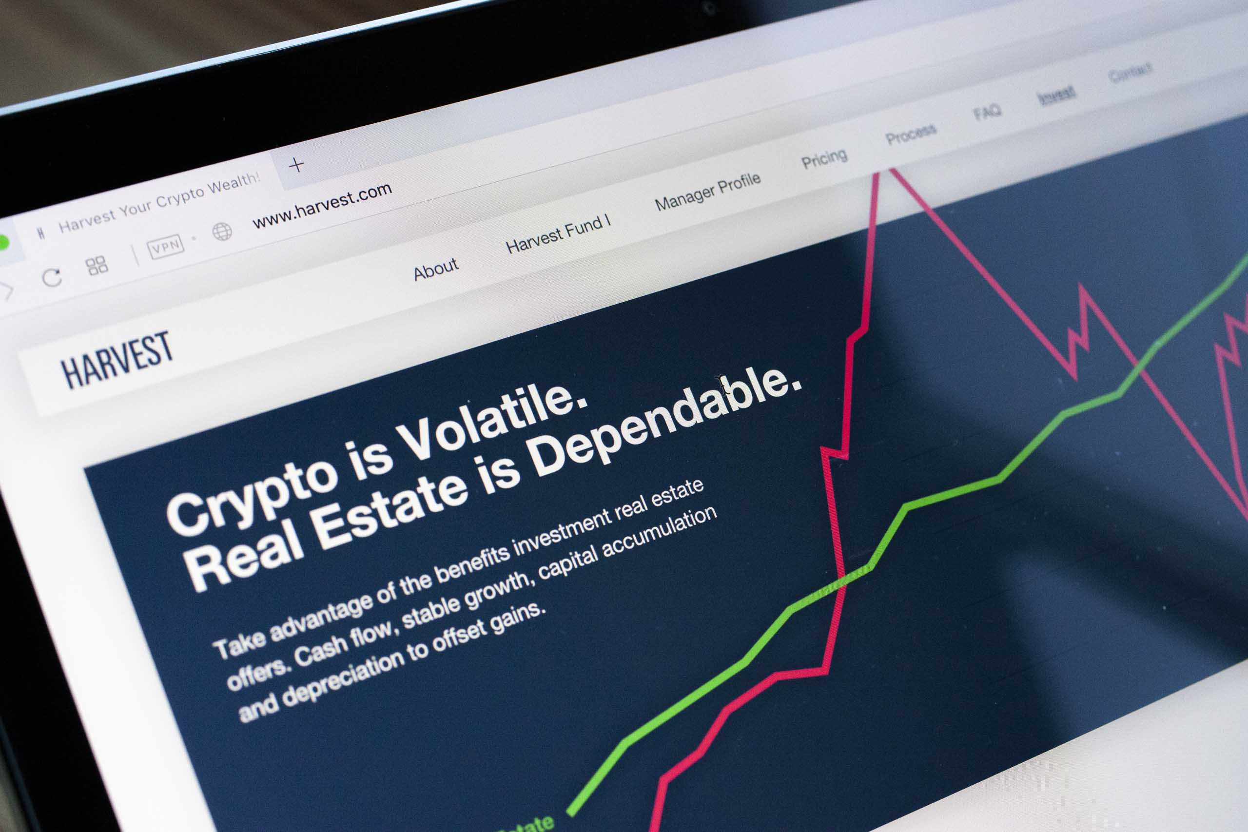 Laptop screen close up photo of the cryptocurrency vs real estate graph — by Yagnyuk.