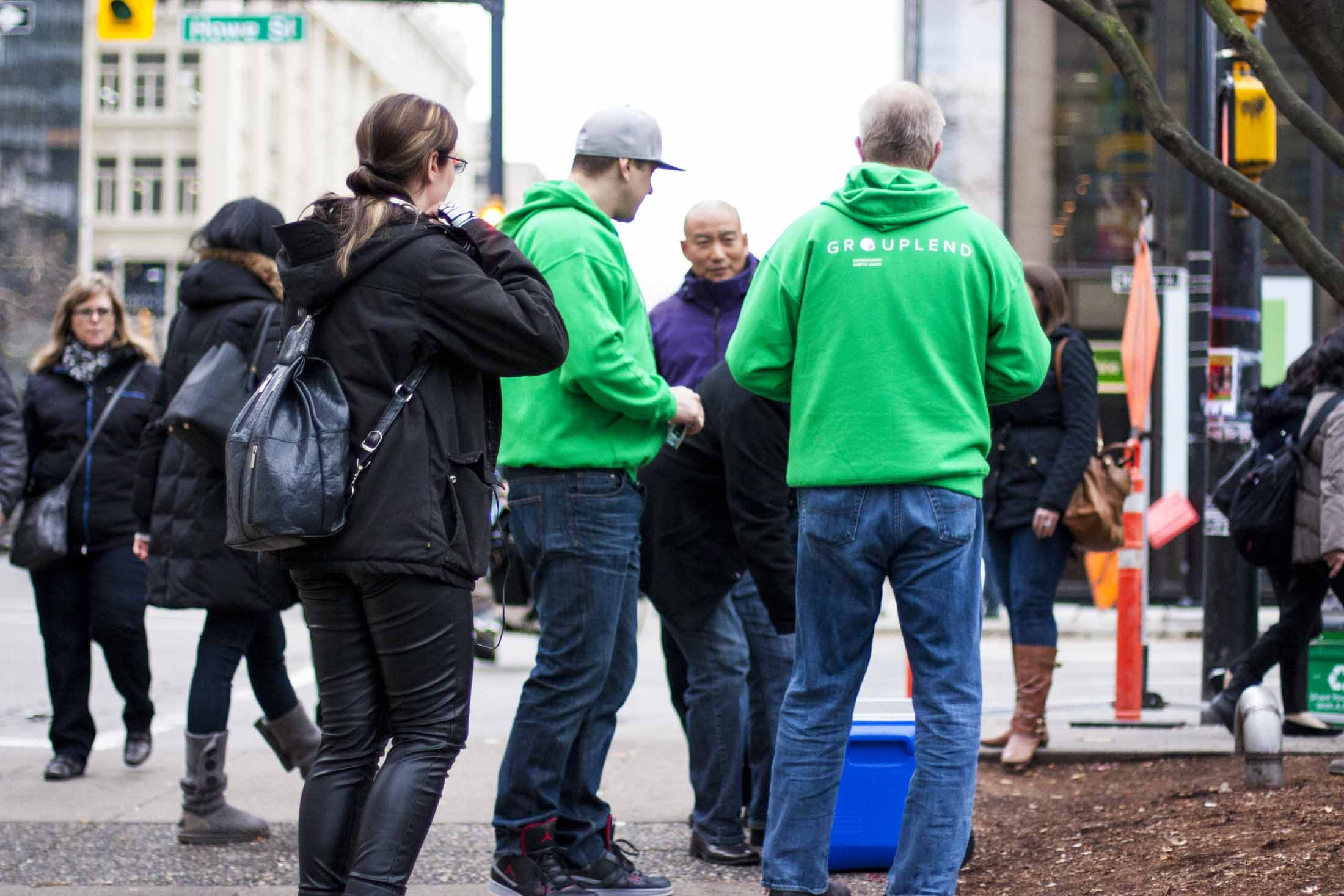 Grouplend team members in neon green branded sweaters at the Vancouver Art Gallery encouraging passerby to participate — by Dima Yagnyuk.