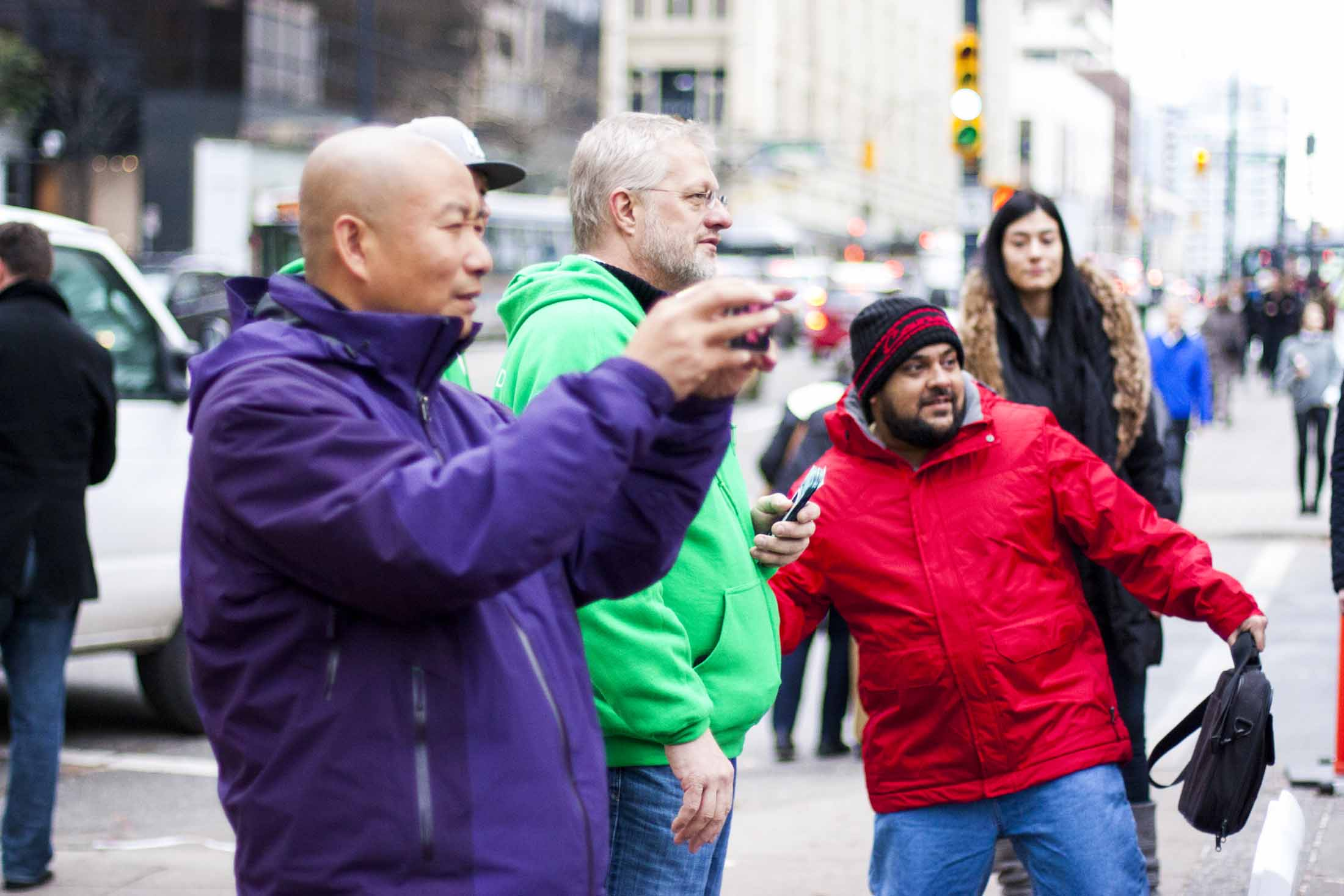 A man in bright red jacket throwing a ballon at the Credit Card costumed Grouplend CEO Kevin Sandhu — by Yagnyuk.