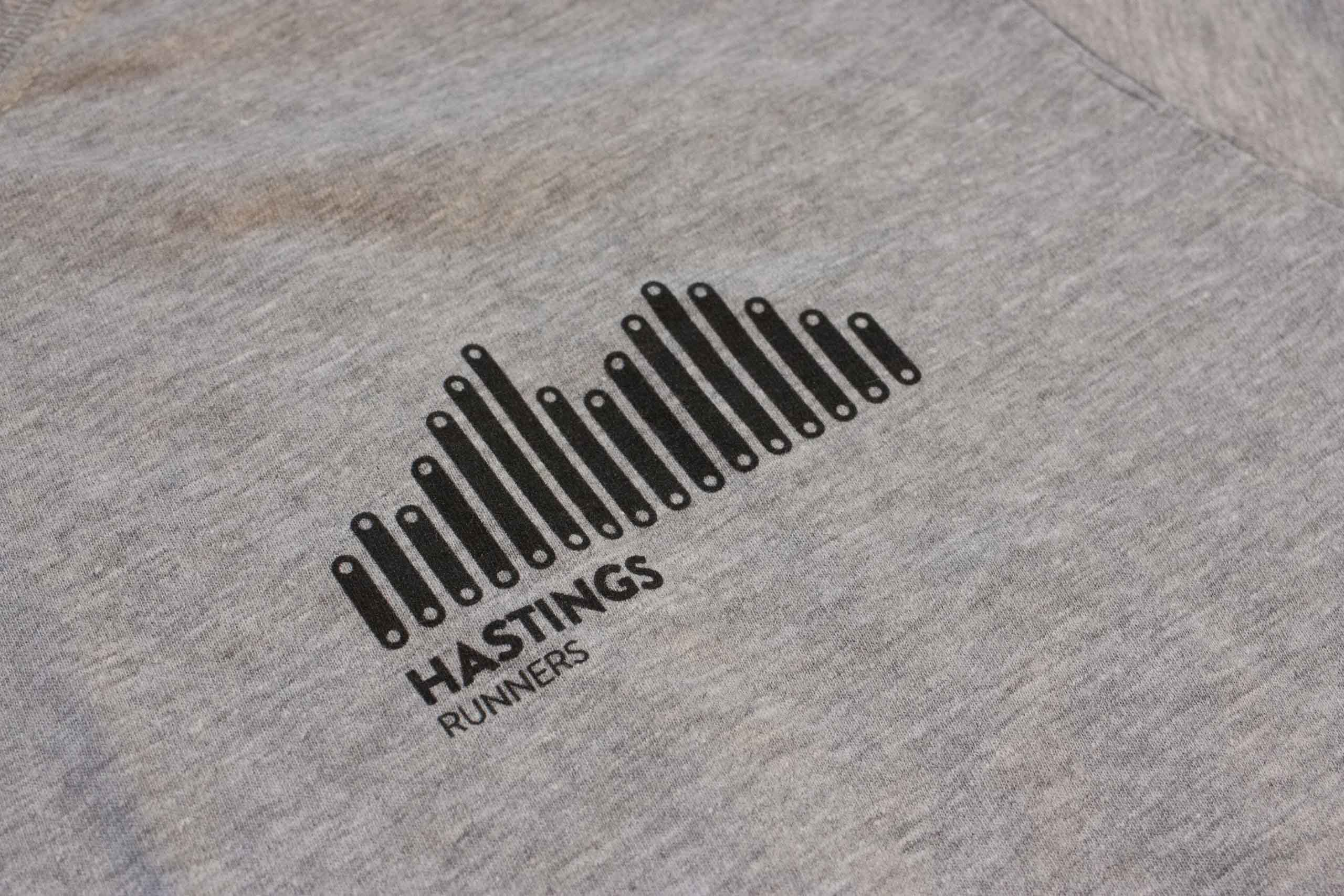 Close of photo of the shirt focused on the Hastings Runners Logo — by Yagnyuk.