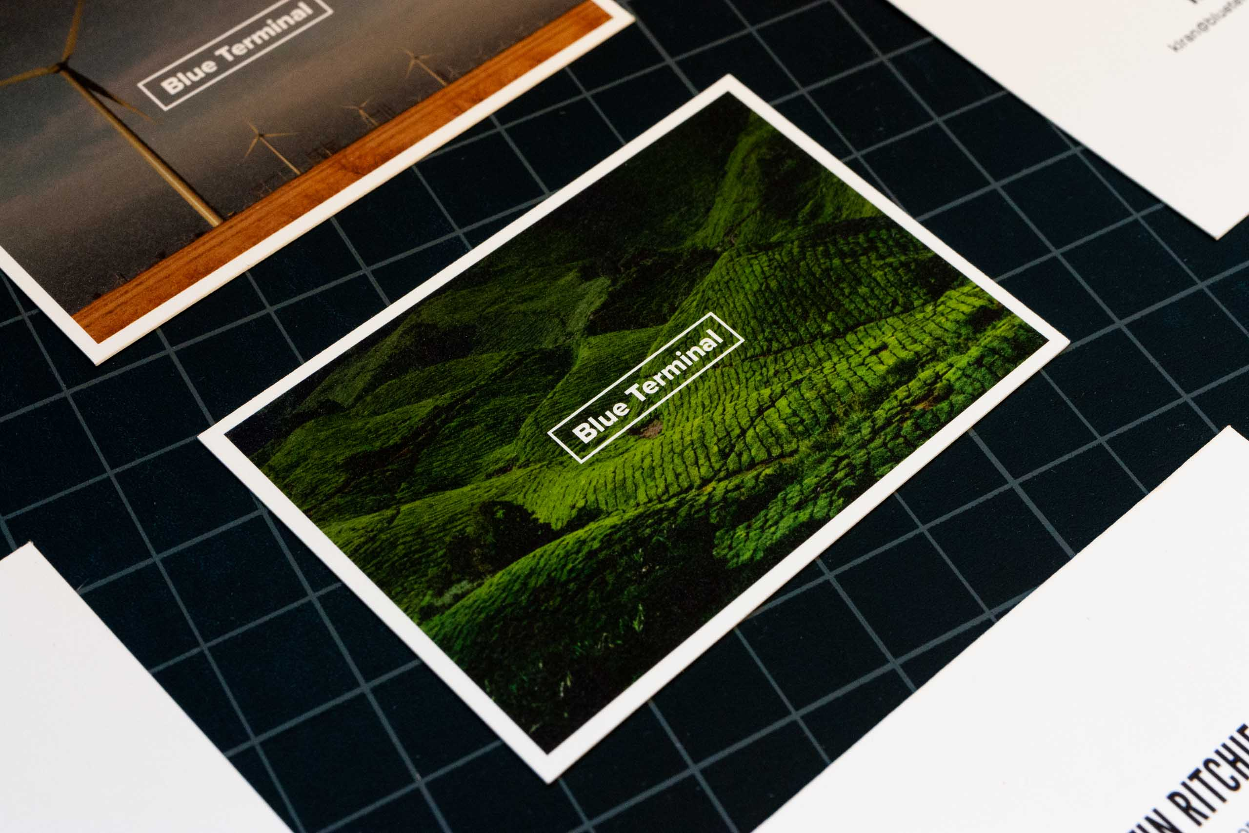 Close up of Blue Terminal business card image side with Blue Terminal logo in white over a photo of green rolling hills — by Yagnyuk.