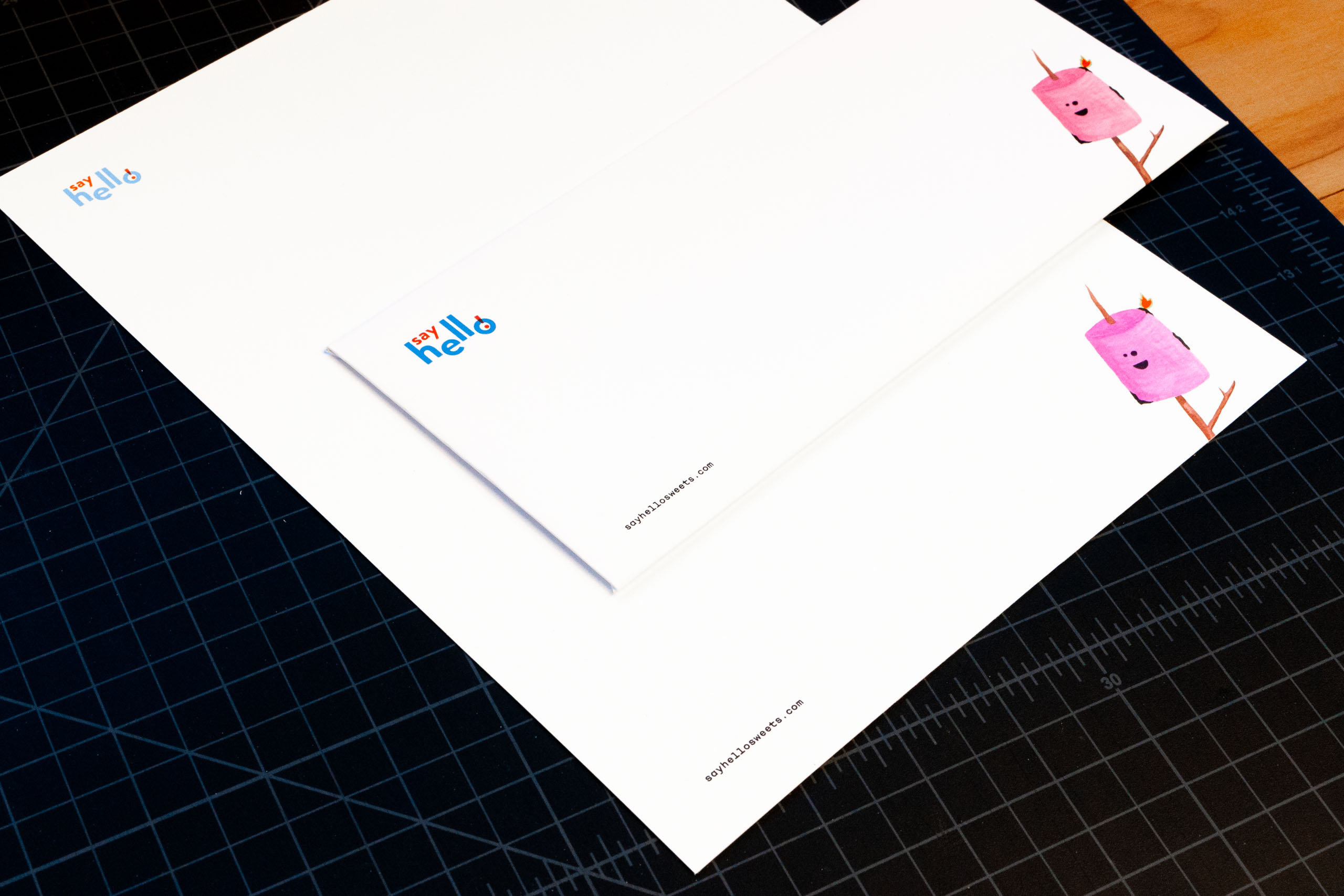 Say Hello business card and letterhead featuring logo in the top left corner looking down to the bottom right corner to see a toasted marshmallow illustration — by Yagnyuk.