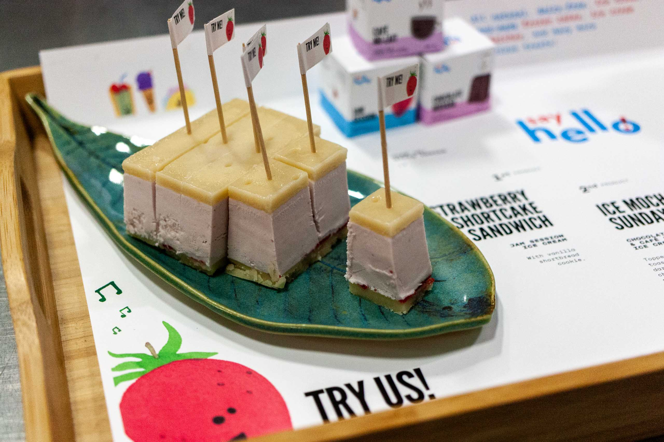 "Close up of turquoise colored plate in a shape of a leaf with a sliced up ice cream sandwich with toothpicks featuring little strawberry ""try me!"" flags — by Dima Yagnyuk."