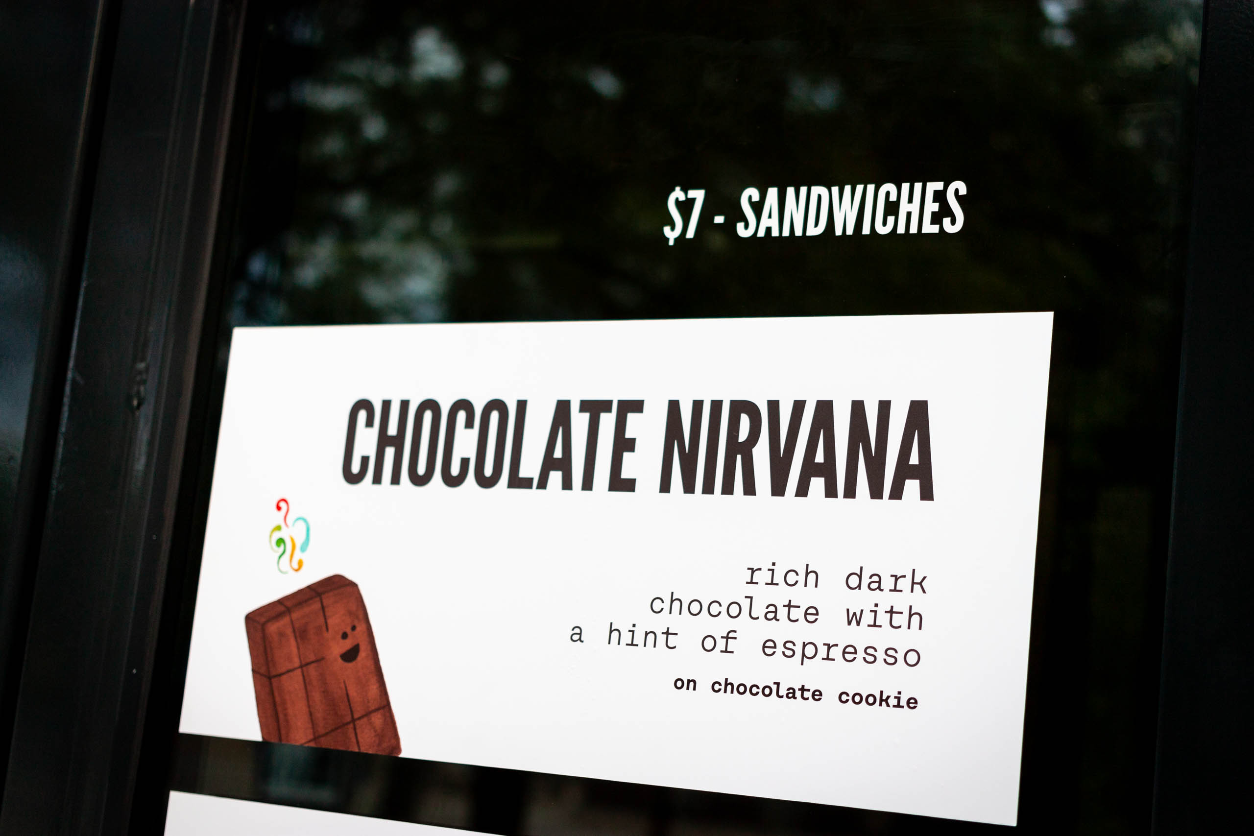 Close up of window display for Say Hello Chocolate Nirvana Ice Cream sandwich with product description and price — by Dima Yagnyuk.