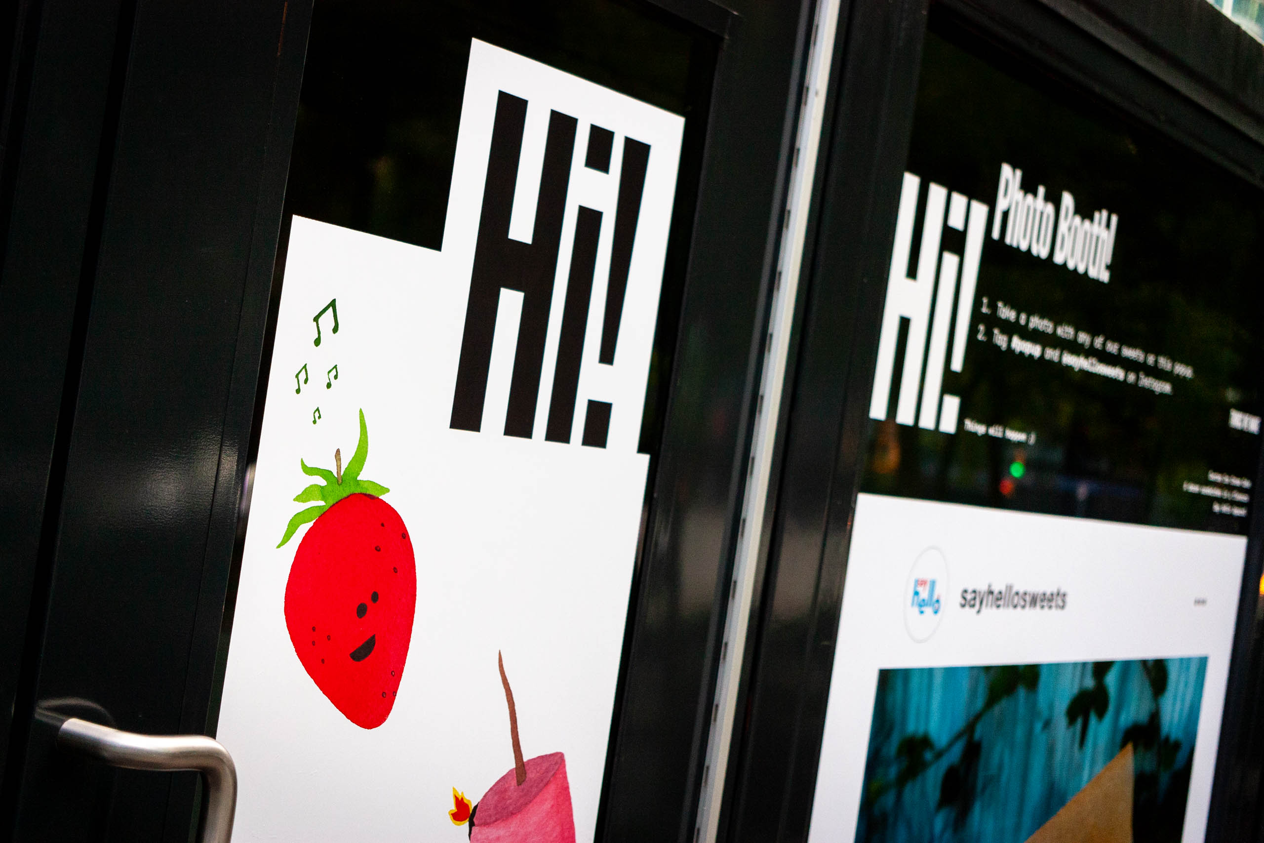 "Close up of the front door vinyls with a large ""Hi"" text greeting and illustrations of strawberry and marshmallow characters — by Dima Yagnyuk."