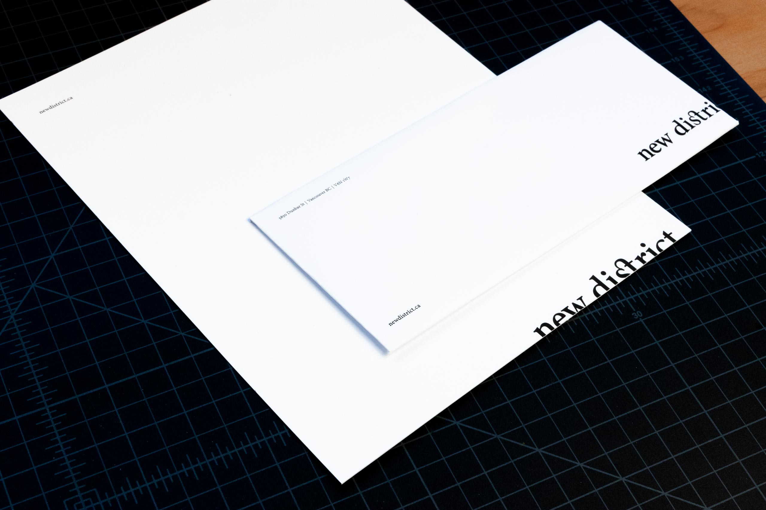 New District envelope and letterhead with logo bleeding of the bottom edge — by Yagnyuk.