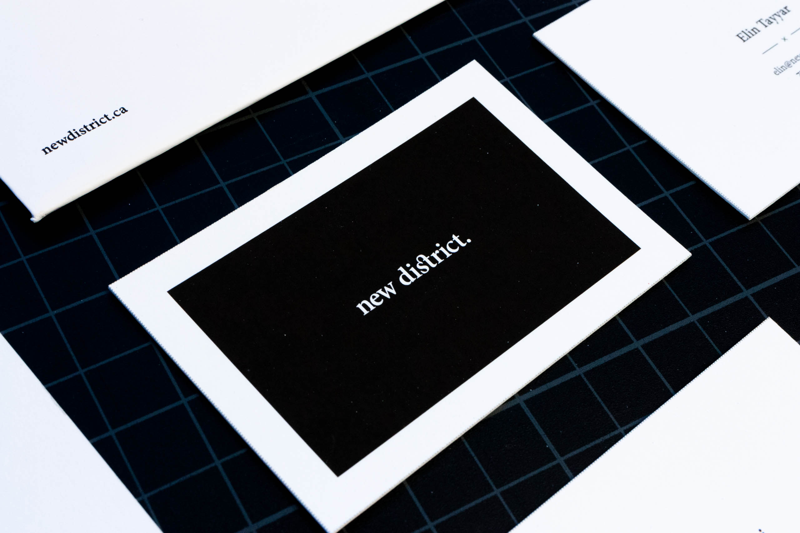 Back of New District business card with the logo in white over a black framed background — by Yagnyuk.