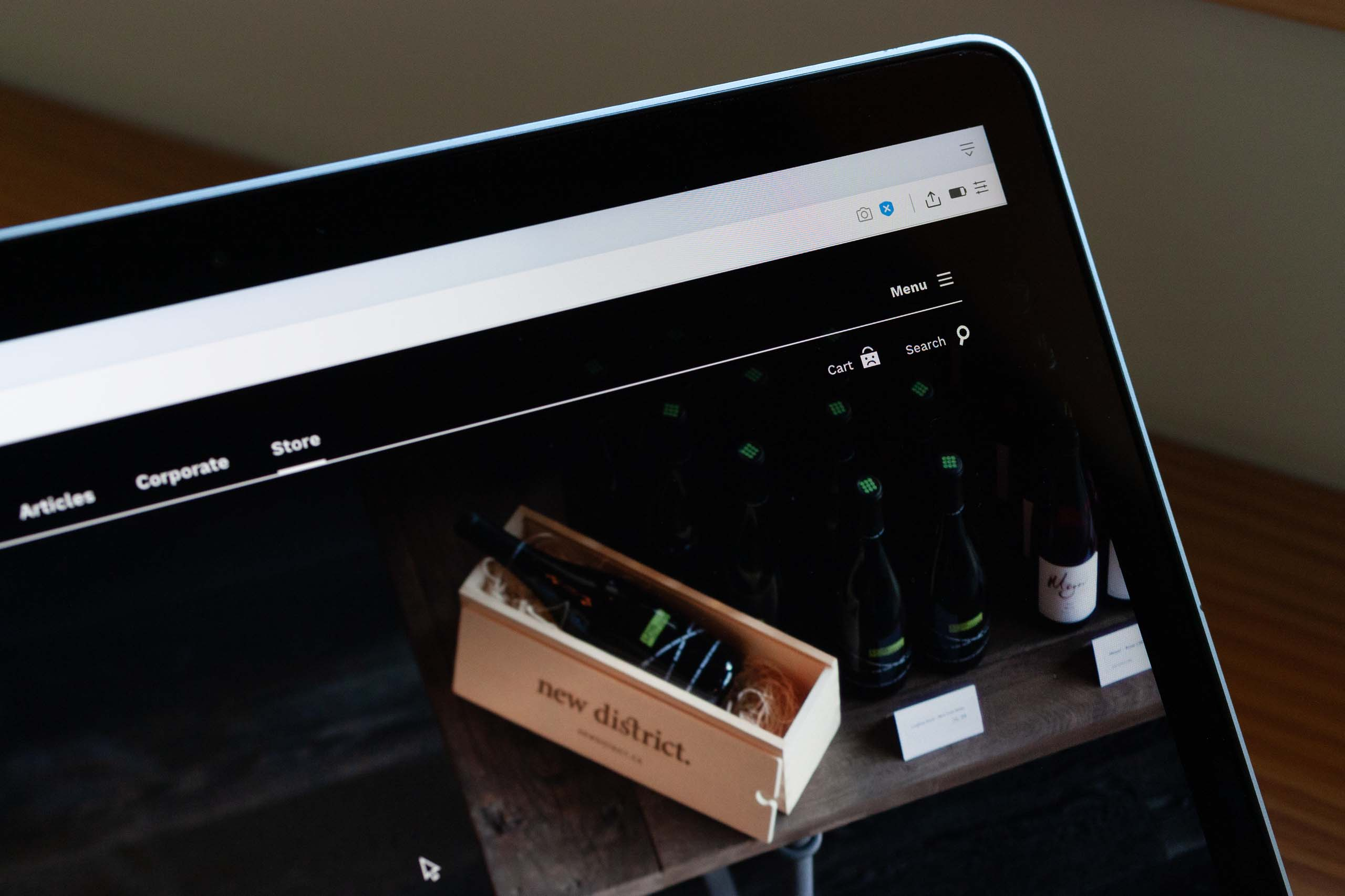 Close up photo of New District Wine store page showing table presentation, with packaging, wine, stained wood table and dark hardwood floors — by Dima Yagnyuk.