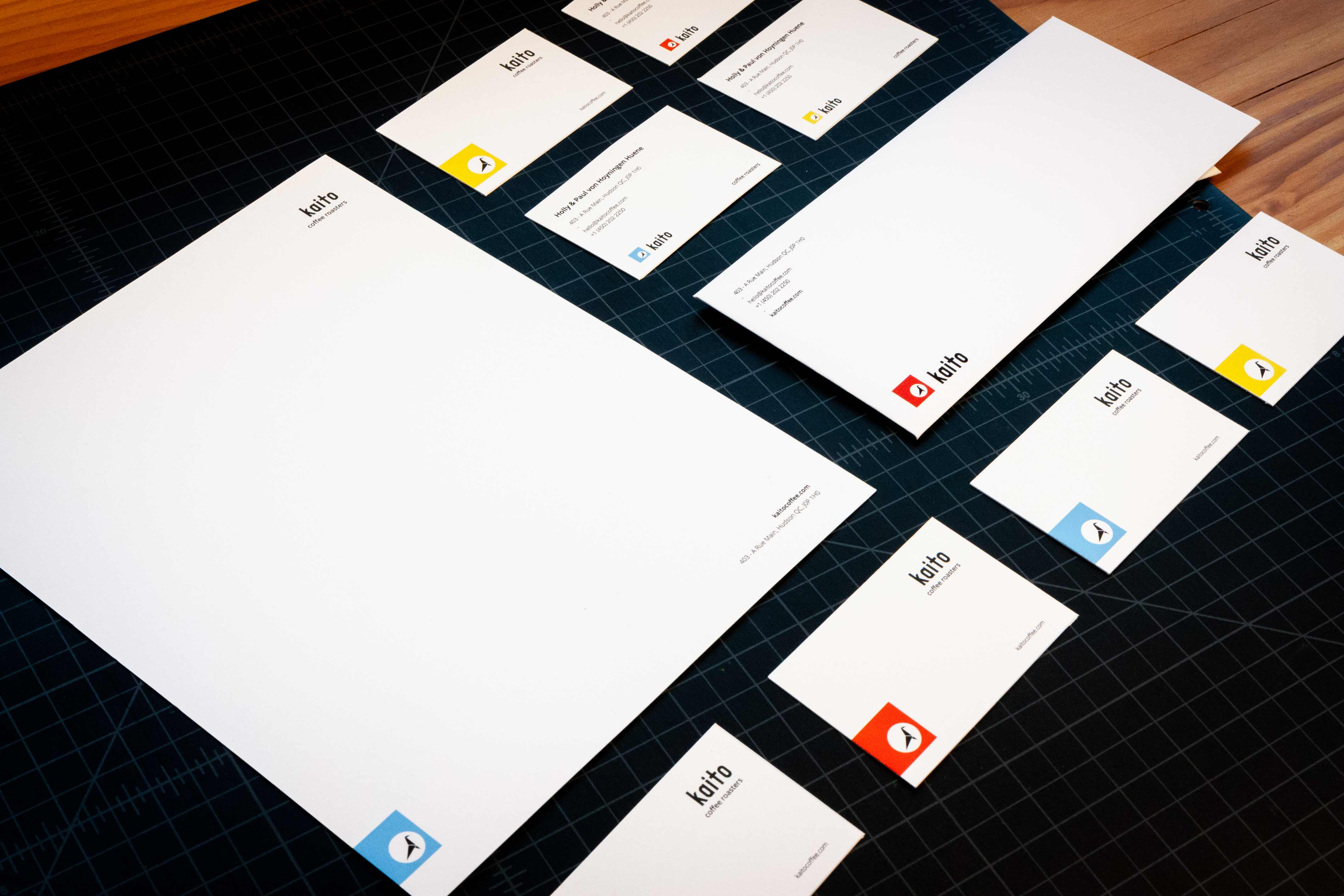 Kaito Coffee letterhead, envelope, and business cards showcasing the bird logo, backed by different colors — by Yagnyuk.
