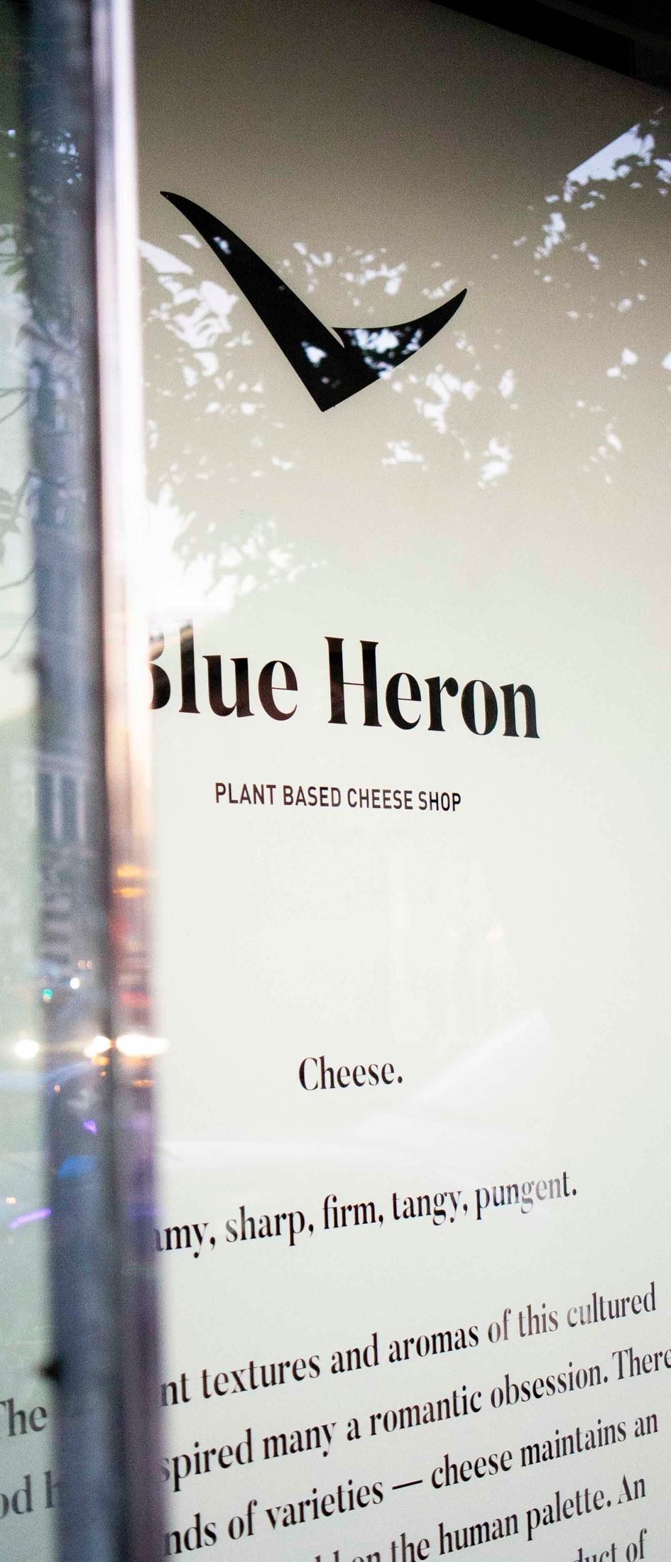 Close up of Blue Heron cheese store windows, showcasing the handpainted logo and brand manifesto — by Dima.