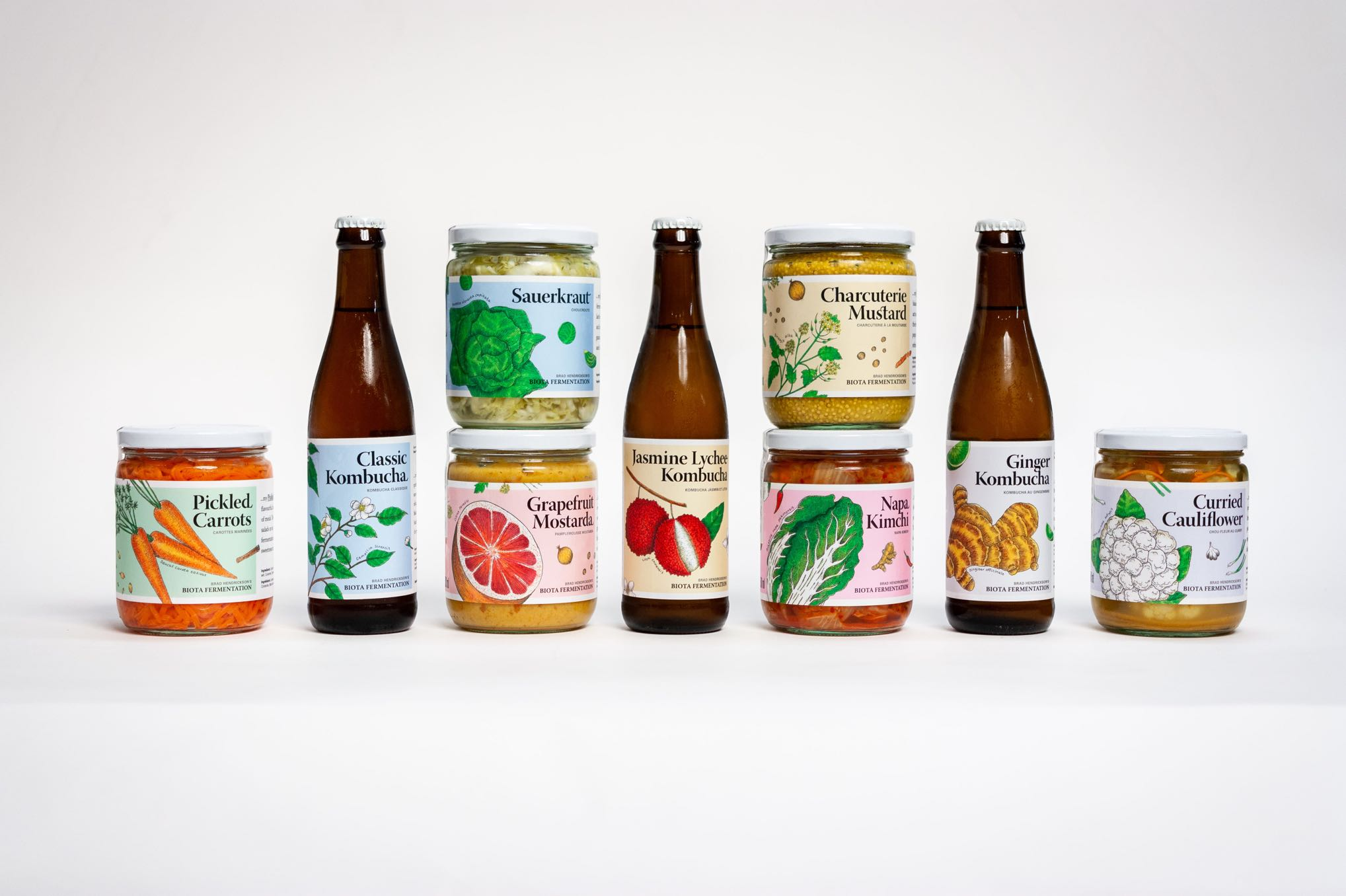 330ml Bottles and 500ml, 250ml Jars of Biota Fermentation kombucha, and various preserves, featuring vibrant, colorful, sharp botanical illustrations of carrots, tea plant, grapefruit, mustard plant, cabbage, lychee, ginger and cauliflower by Jessica Fraser — by Dima Yagnyuk.