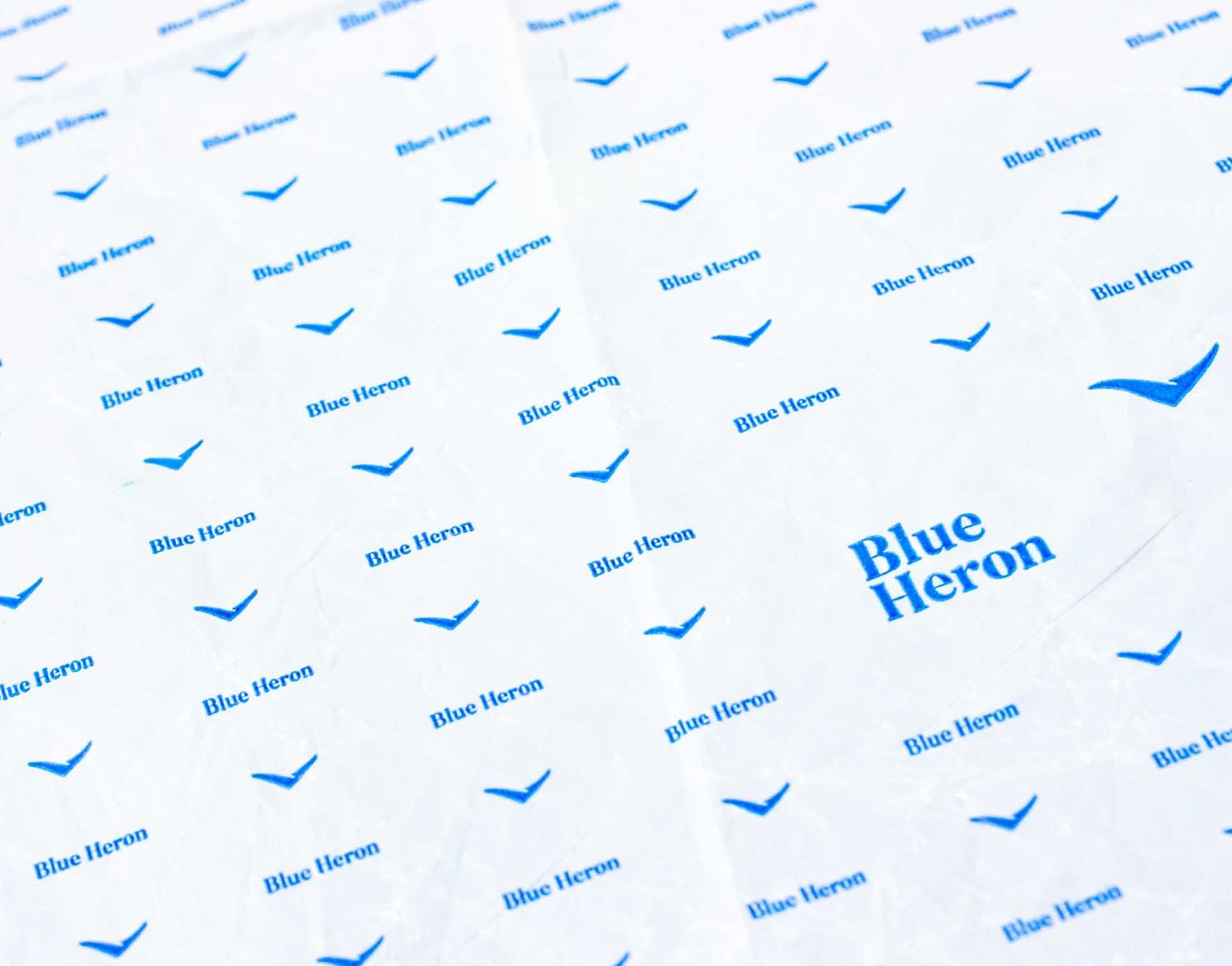 Blue Heron's pantone matched brand blue, elegant, shelf-life extending cheese paper featuring a patterned Blue Heron logo with accompanying brandmark — by Dima Yagnyuk.