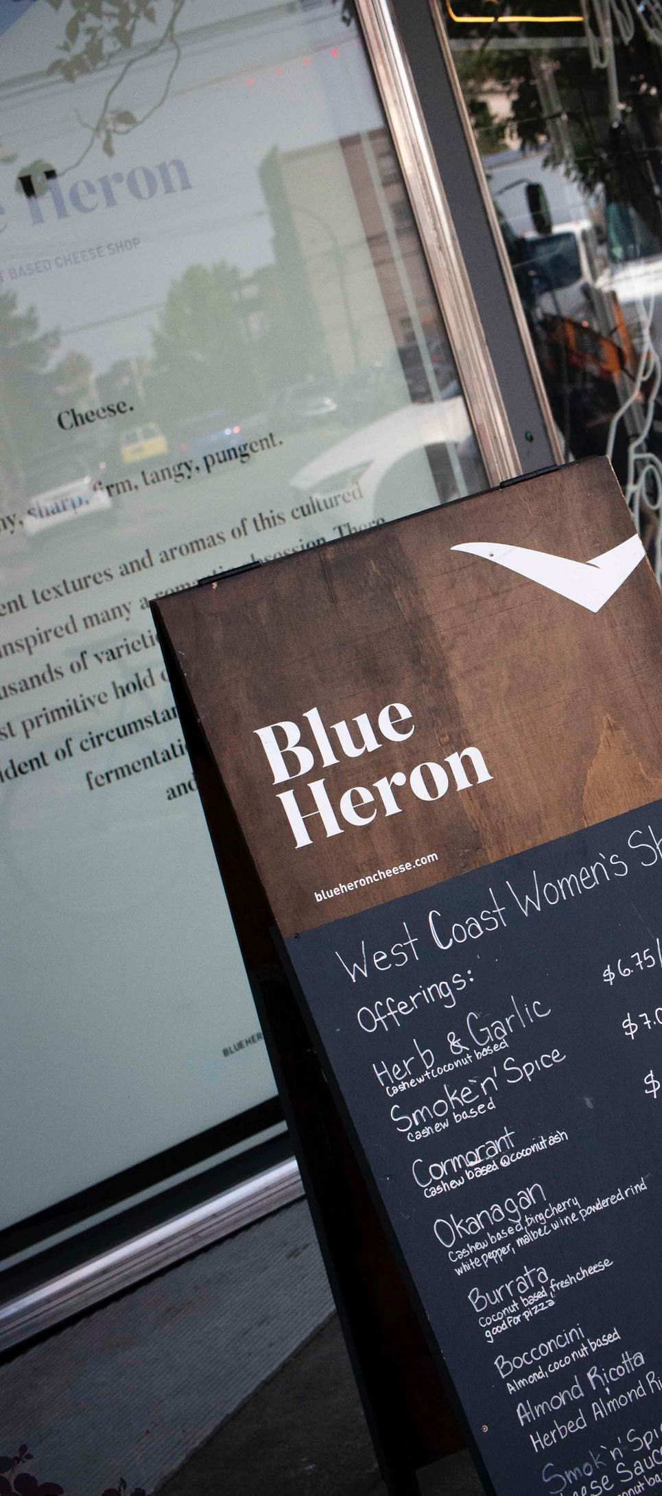 Blue Heron Storefront with store windows featuring a handsigned brand manifesto with branding applied to a sandwich board placed next to it — by Dima Yagnyuk.