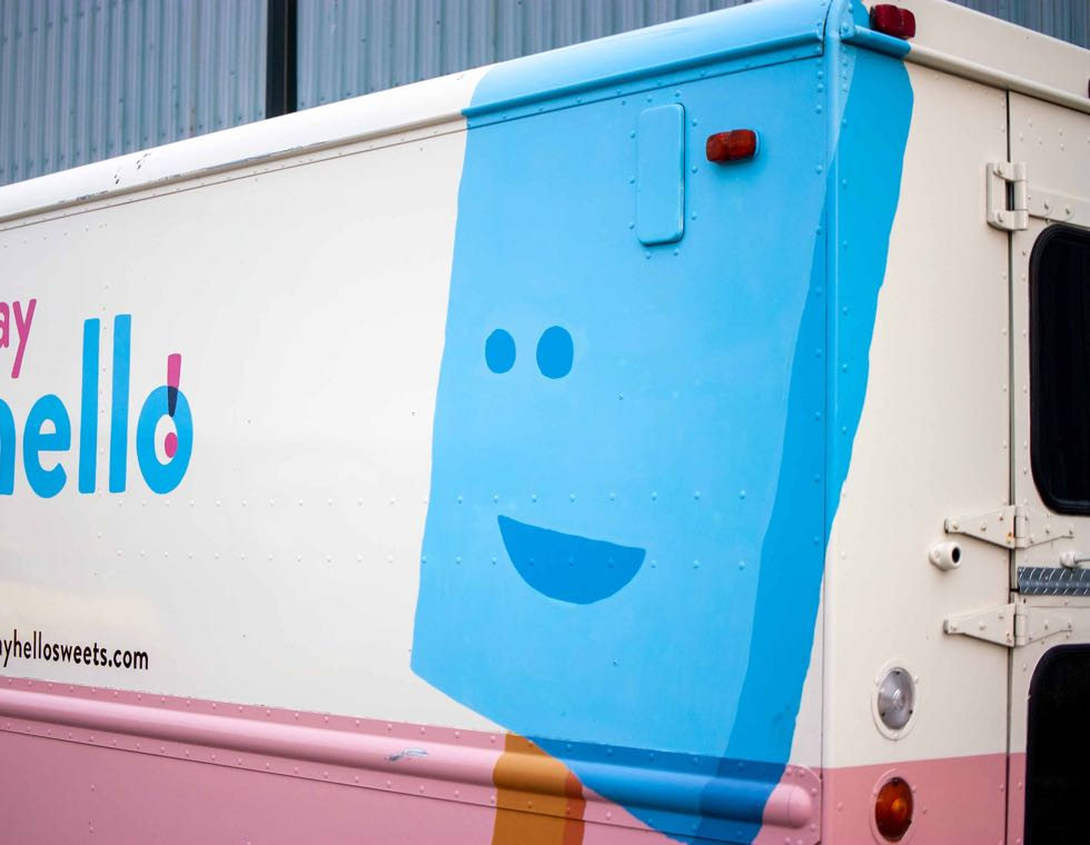 Say Hello Sweets truck featuring a handsigned, blue wrap around ice cream bar with a cartoon face — by Yagnyuk.