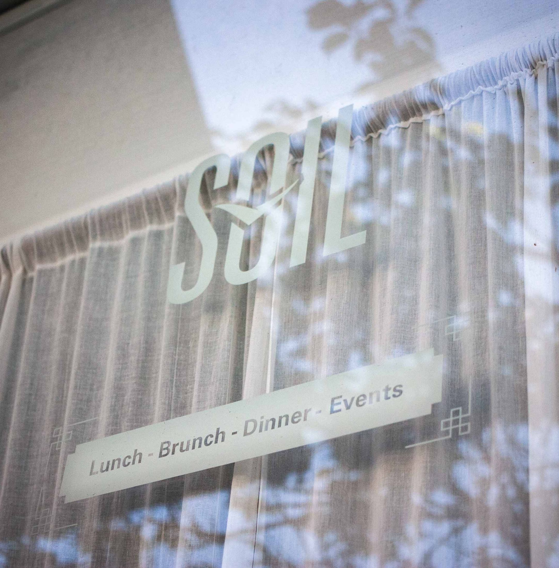 Soil Restaurant window close up featuring the logo in front curtained interior — by Dima Yagnyuk.