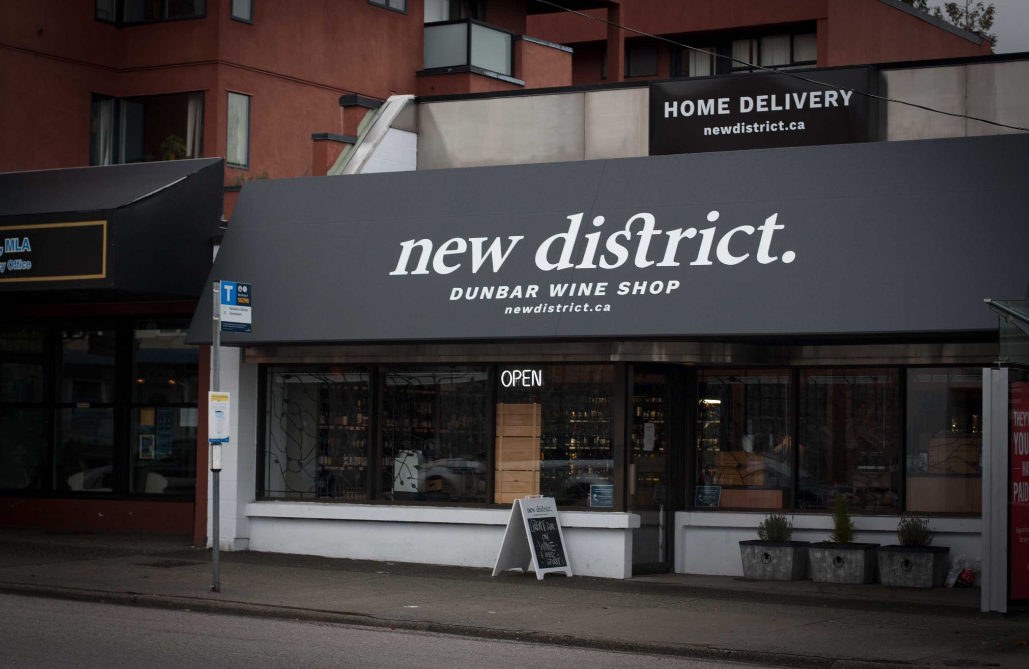 New District Storefront featuring black and white awnings with contrasting logo — by Yagnyuk.