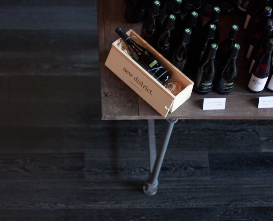 New District wine store interior setup showcasing table with branded packaging next to wine display — by Yagnyuk.