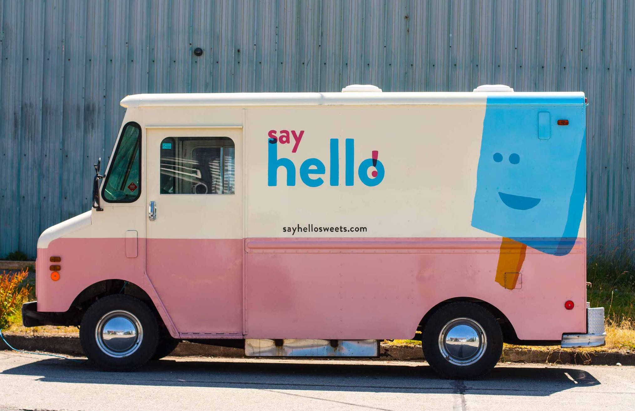 Say Hello Ice Cream Truck side profile showing pink and white exterior with vibrant blue brandmark and ice cream bar character — by Dima.