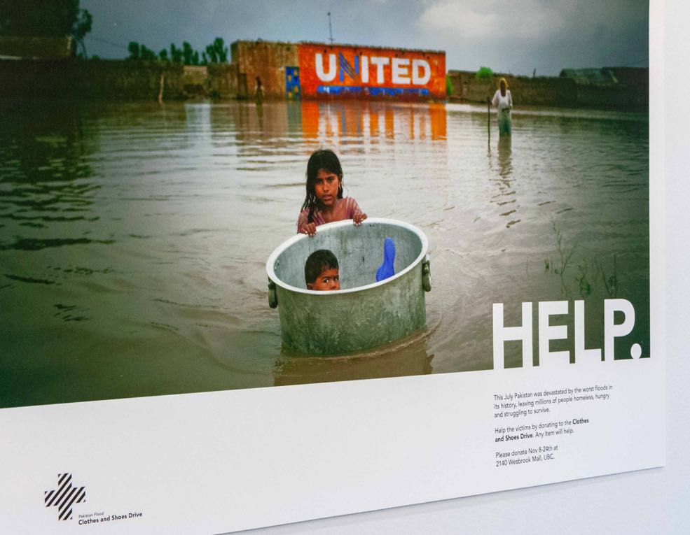 A young boy in a large pot, floating pushed by a young girl through a flooded town in Pakistan — by Dima Yagnyuk.