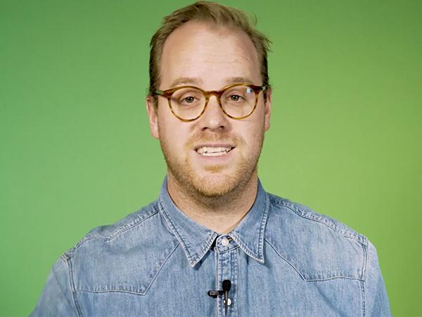 Thumbnail blogartikel beurs- of eventvideo - man met bril die recht in de camera kijkt