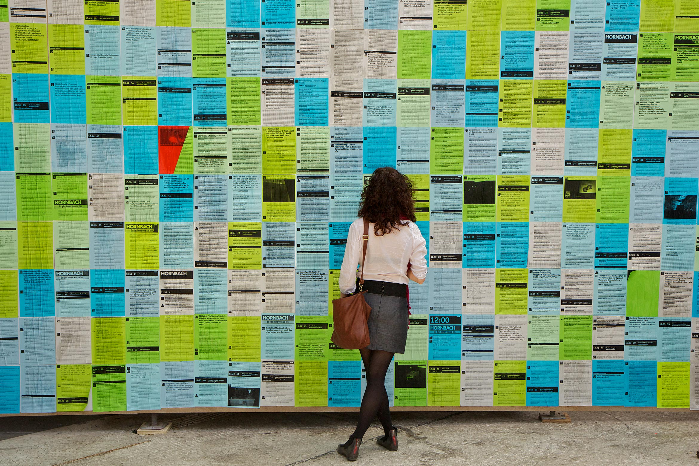 A conference visitor in front of the analog twitter wall reading tweets.