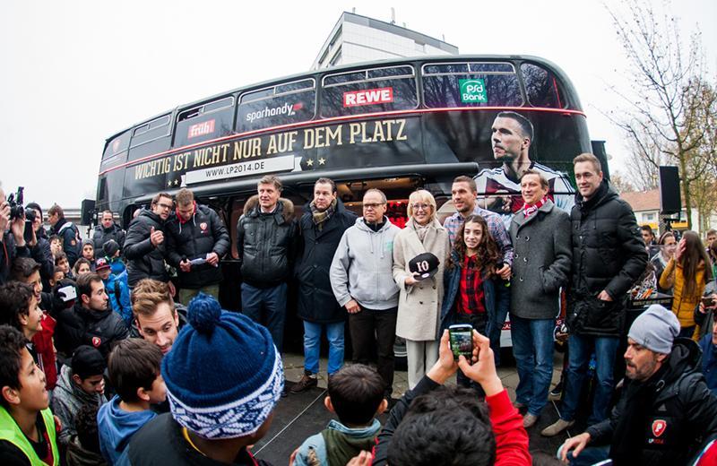 Lukas Podolski, Elfi Scho-Antwerpes und Sponsoren vor dem LP2014-Bus