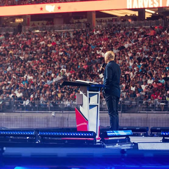Greg Laurie standing on stage talking to thousands of people.