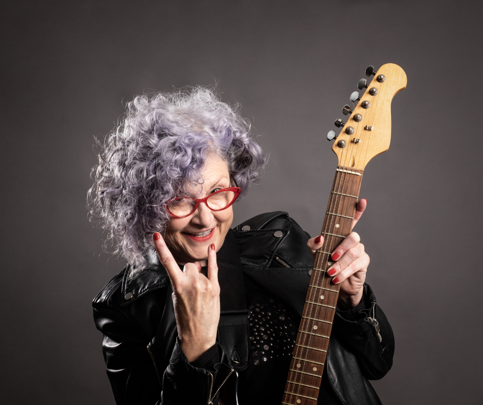 A smiling woman holding a bass guitar