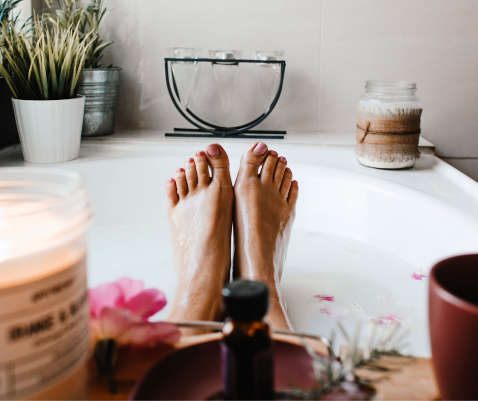 A woman's feet displayed in a bathtub surrounded by plants and candles