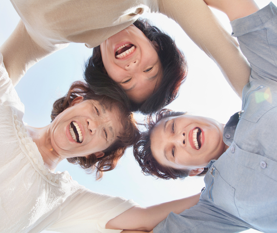 Inverted photo of three smiling women joined together arm-in-arm